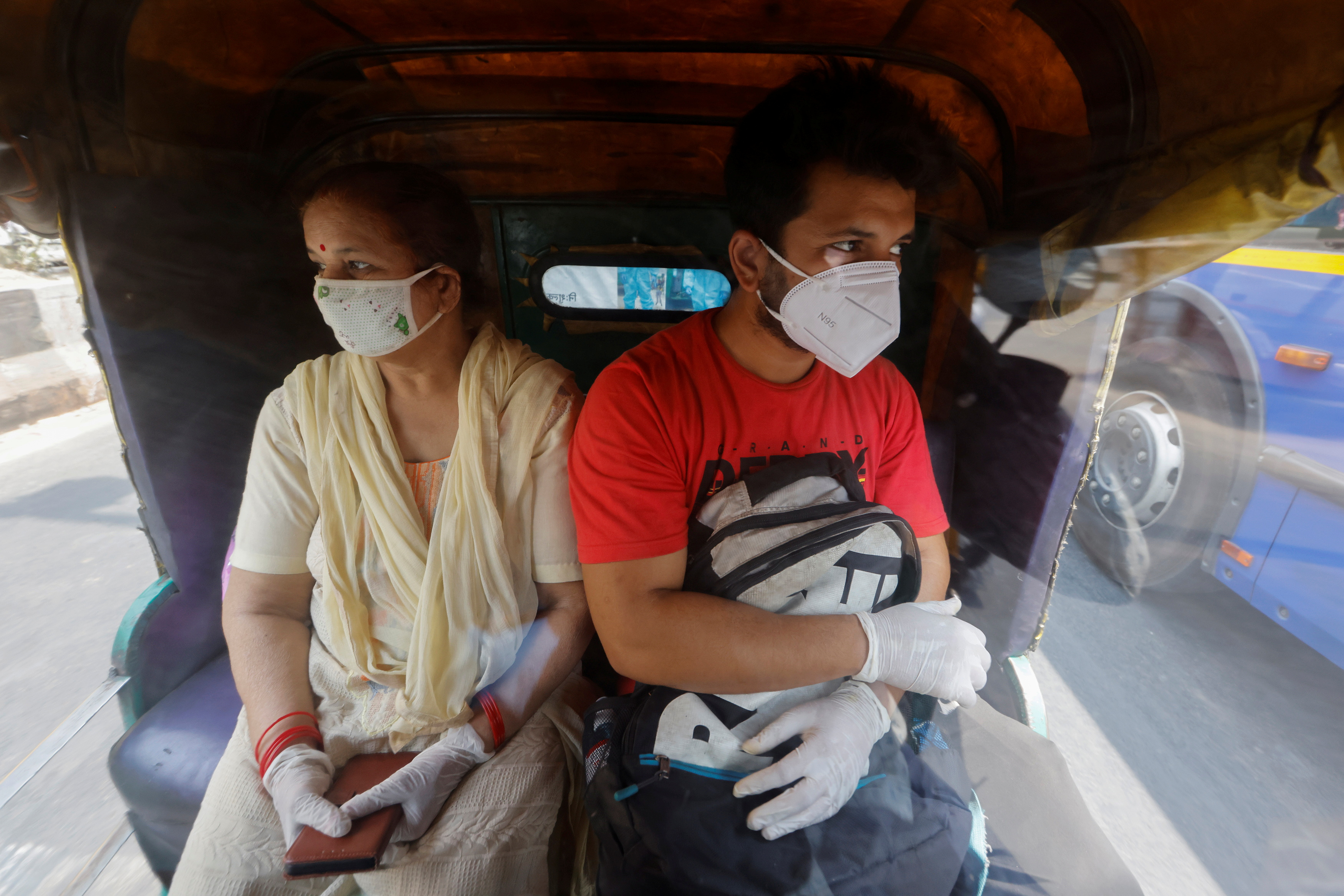 Rahul Malhotra, whose father is admitted in Lok Nayak Jai Prakash Narayan Hospital (LNJP), one of India's largest facilities for coronavirus disease (COVID-19) patients only, and his mother, ride an auto rickshaw ambulance prepared to transfer people suffering from the disease and their relatives for free, in New Delhi, India May 6, 2021. REUTERS/Adnan Abidi