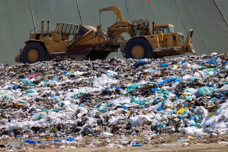 Workers use heavy machinery to move trash and waste at the Frank R. Bowerman landfill on Irvine, California, U.S., June 15, 2021.Picture taken June 15, 2021.     REUTERS/Mike Blake