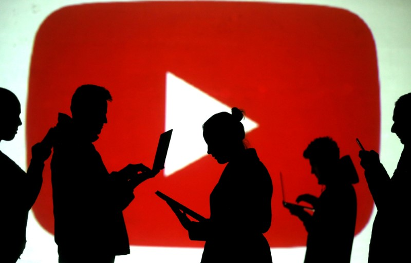 Silhouettes of laptop and mobile device users are seen next to a screen projection of the YouTube logo in this picture illustration taken March 28, 2018. REUTERS/Dado Ruvic