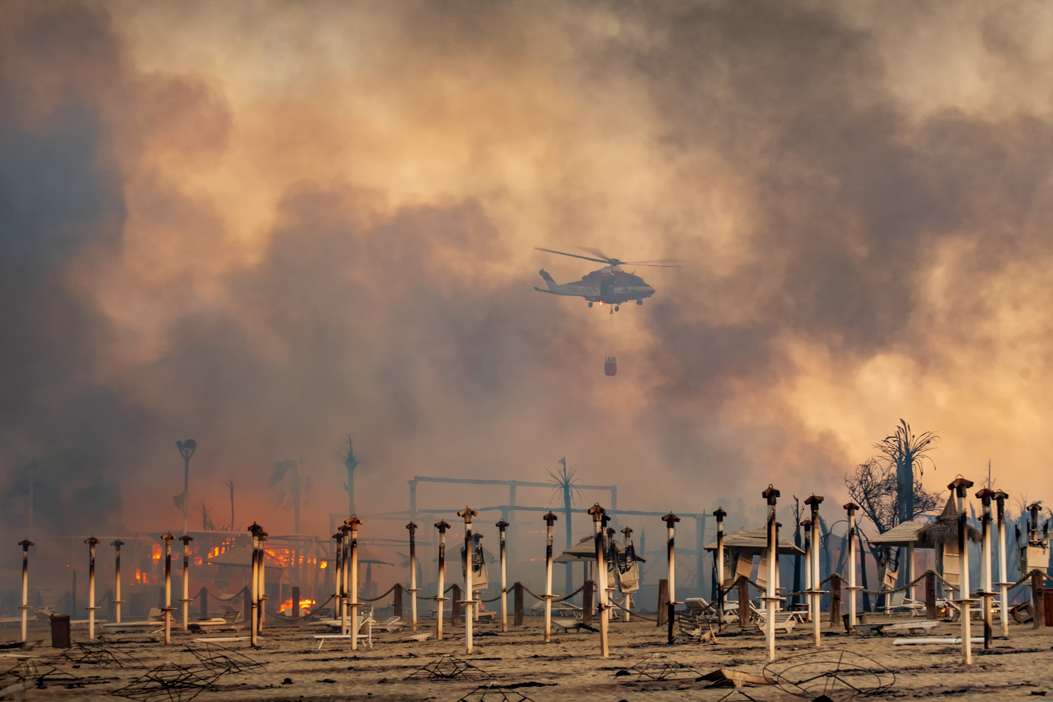 A helicopter flies above a fire at Le Capannine beach in Catania, Sicily, Italy, July 30, 2021, in this photo obtained from social media on July 31, 2021.  Roberto Viglianisi/via REUTERS