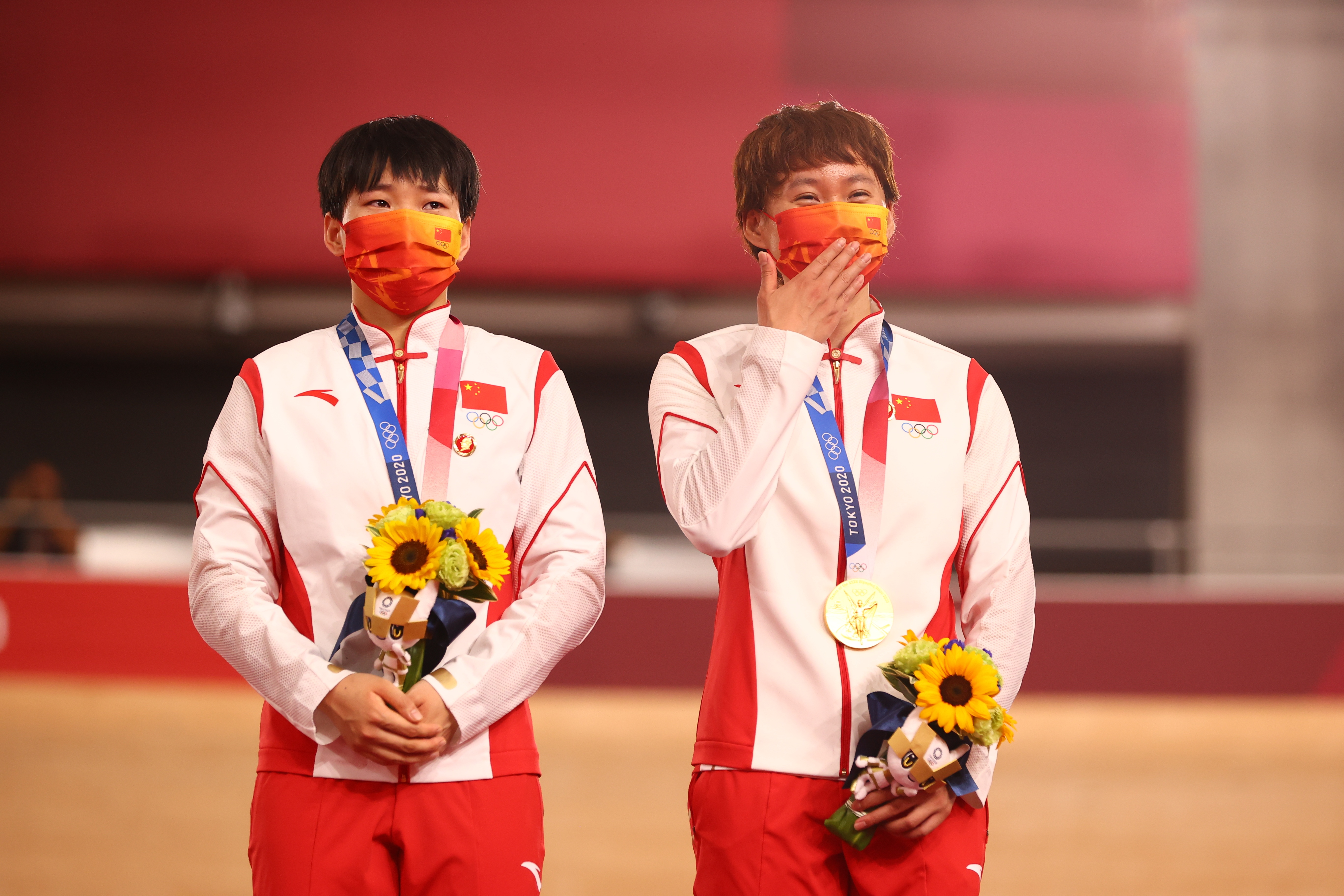 Tokyo 2020 Olympics - Cycling - Track - Women's Team Sprint - Medal Ceremony - Izu Velodrome, Shizuoka, Japan - August 2, 2021.  Gold medallists Bao Shanju of China and Zhong Tianshi of China wearing protective face masks pose with badges of the late Chinese chairman Mao Zedong pinned to their tracksuits REUTERS/Matthew Childs