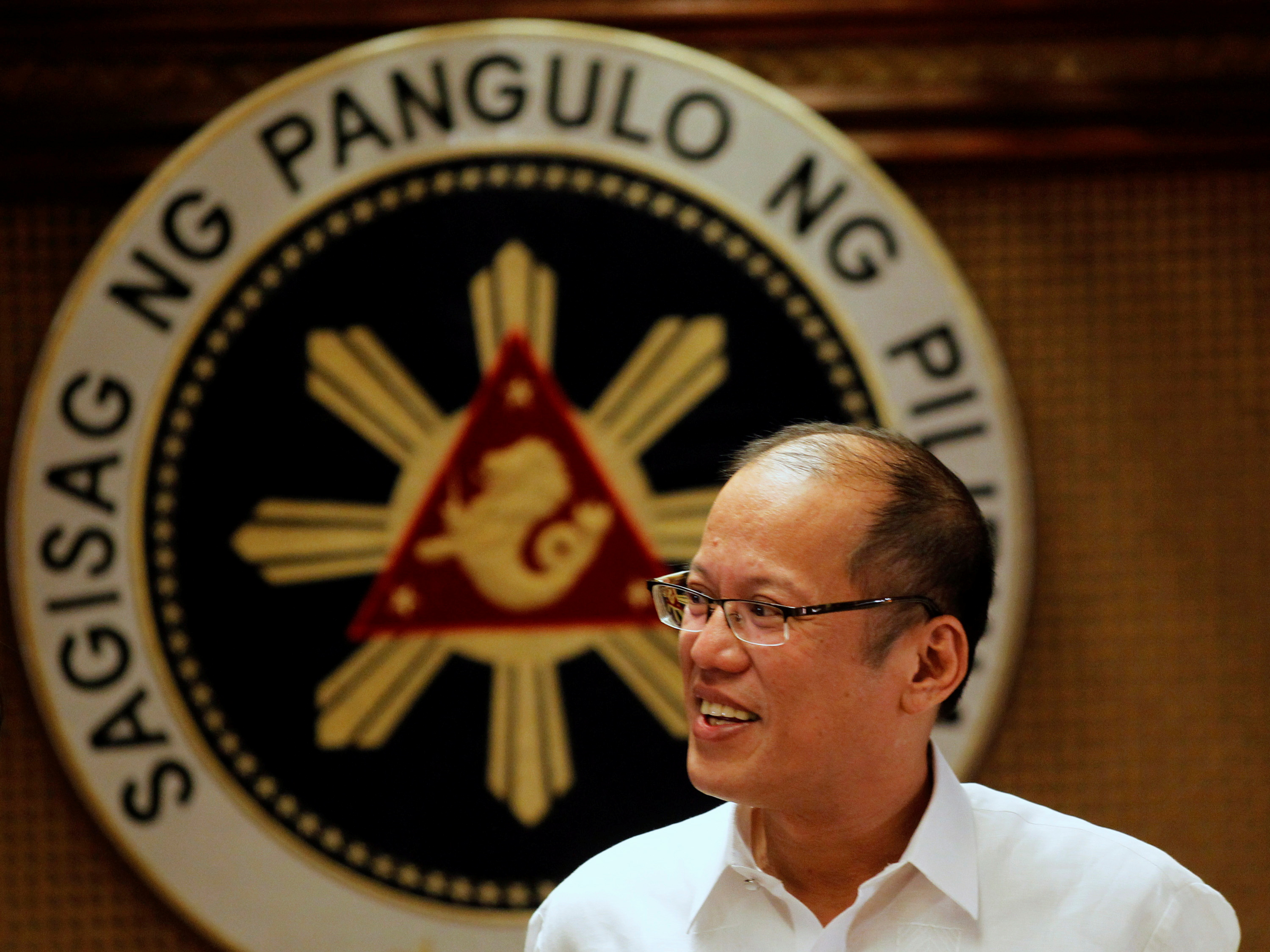 FILE PHOTO - Philippine President Benigno Aquino smiles in front of a presidential seal during a government's oral immunization program for poor families at the presidential palace in Manila July 2, 2012.  REUTERS/Erik De Castro/File Picture