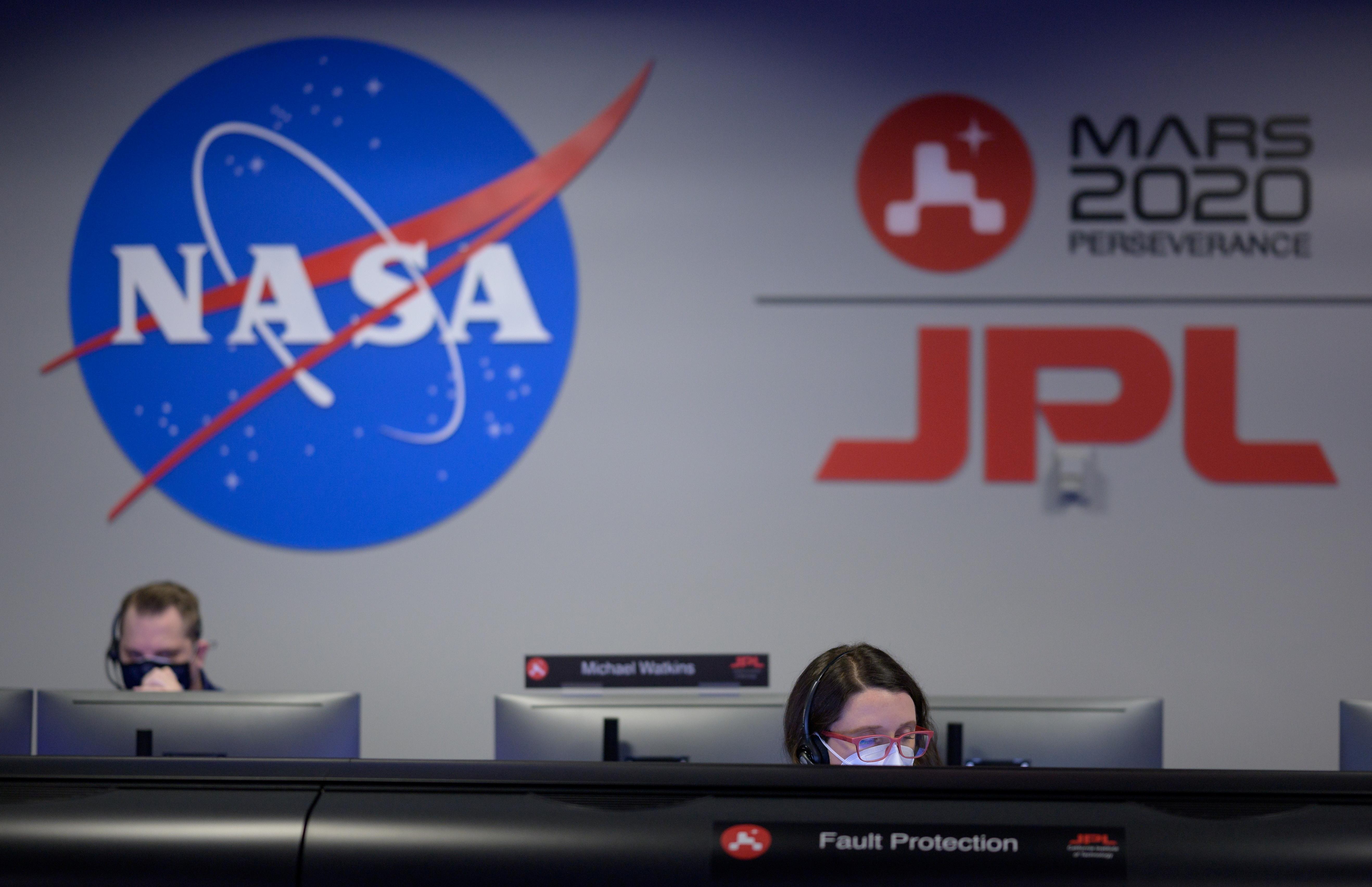 Members of NASA's Perseverance Mars rover team study data on monitors in mission control at NASA's Jet Propulsion Laboratory in Pasadena, California, U.S. February 18, 2021.    NASA/Bill Ingalls/Handout via REUTERS