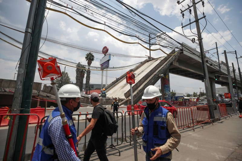 Employees work as part of the investigations in front of the site where an overpass for a metro partially collapsed with train cars on it, in Mexico City, Mexico May 19, 2021. REUTERS/ Henry Romero/File Photo