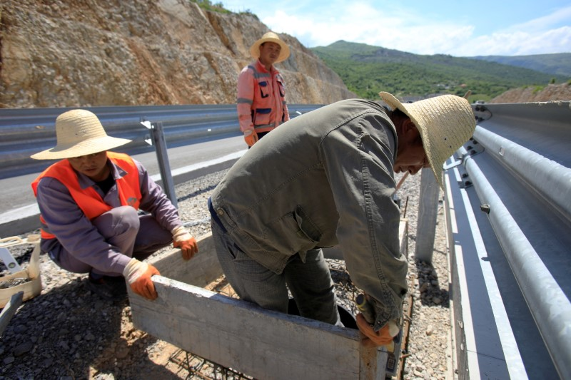 Workers fit a manhole on the Bar-Boljare section of a new highway in Montenegro financed with a large Chinese loan, May 27, 2021. REUTERS/Stevo Vasiljevic/File Photo