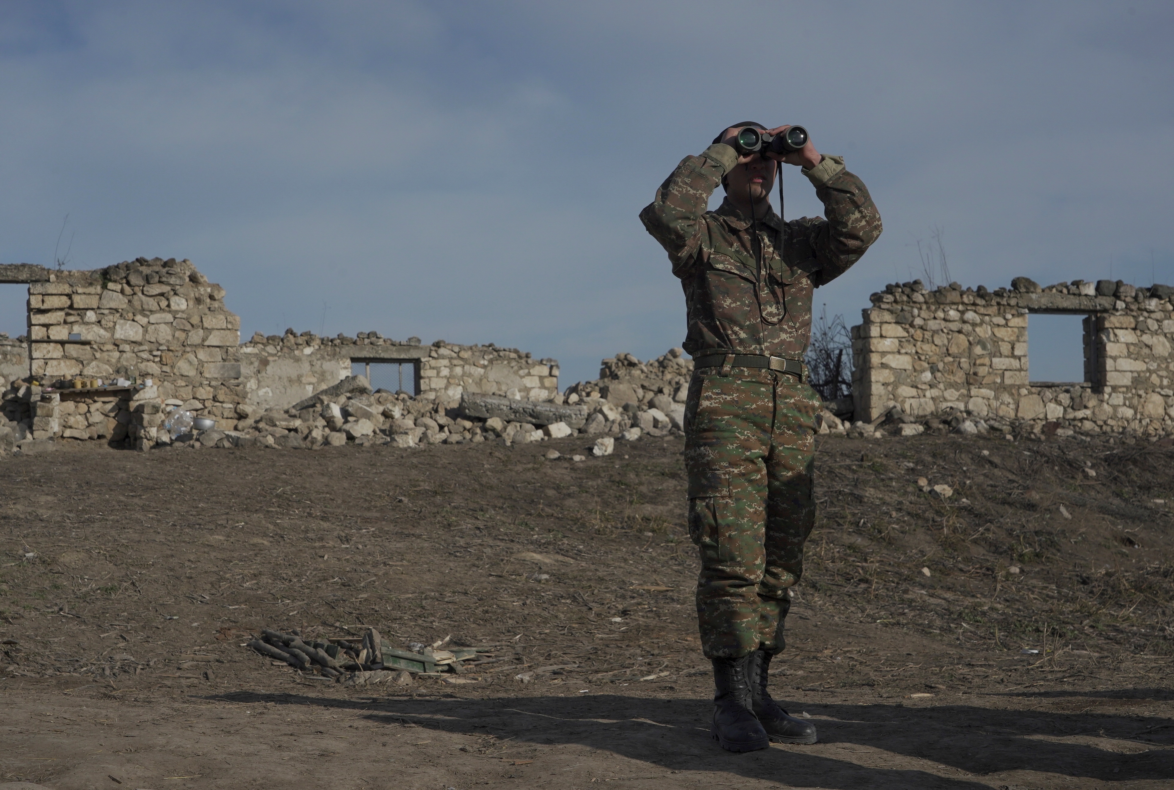 An ethnic Armenian soldier looks through binoculars as he stands at fighting positions near the village of Taghavard in the region of Nagorno-Karabakh, January 11, 2021. Picture taken January 11, 2021. REUTERS/Artem Mikryukov
