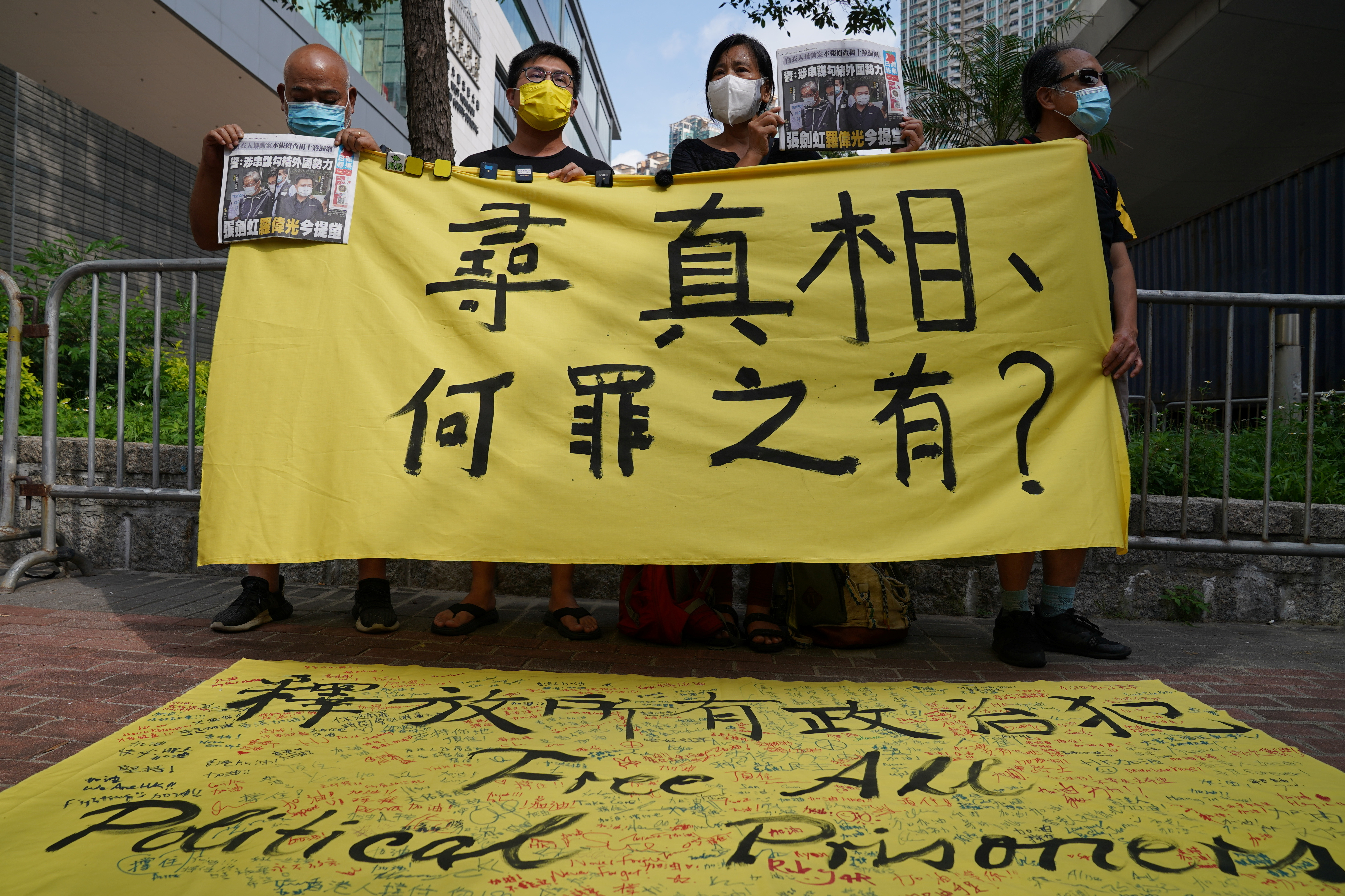 Supporters hold a copies of Apple Daily newspaper and a banner during a court hearing outside West Magistrates' Courts, after police charge two executives of the pro-democracy Apple Daily newspaper over the national security law, in Hong Kong, China, June 19, 2021. REUTERS/Lam Yik