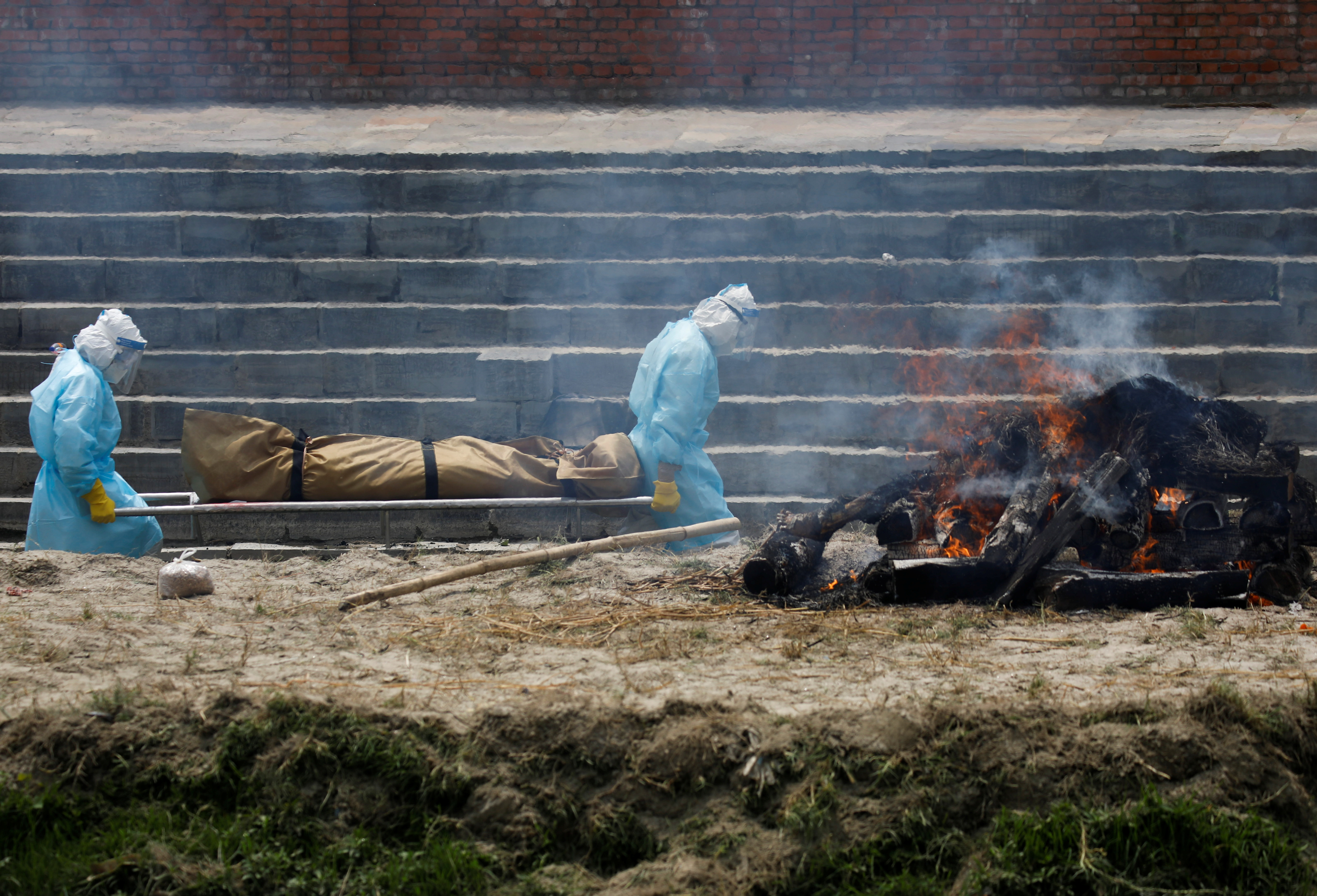 Men wearing personal protective equipment (PPE) carry the body of a COVID-19 victim for cremation on the bank of Bagmati River, as the number of deaths increases amid the spread of the coronavirus disease (COVID-19) in Kathmandu, Nepal May 3, 2021. REUTERS/Navesh Chitrakar