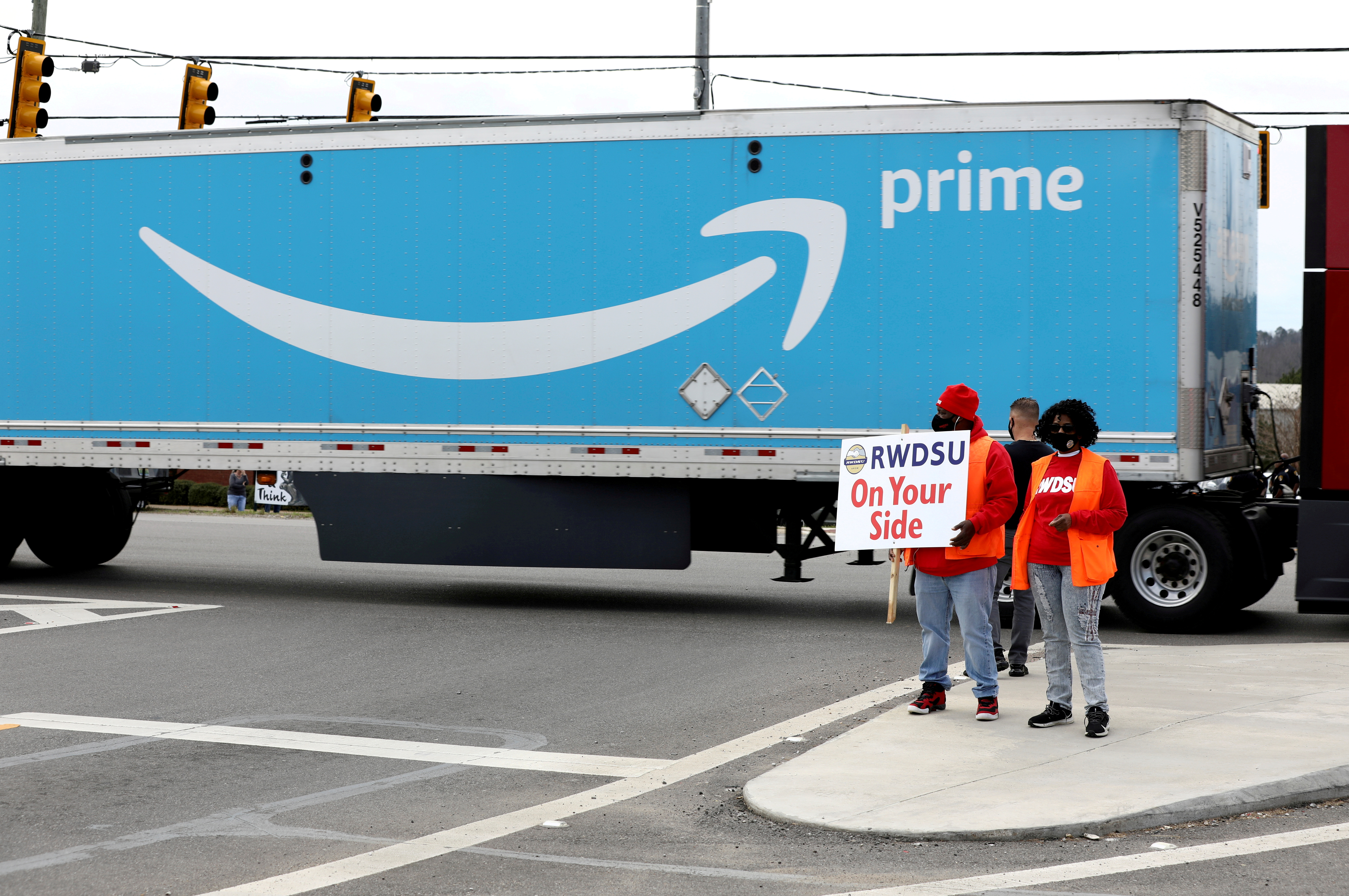 People hold a banner at the Amazon facility as members of a congressional delegation arrive to show their support for workers who will vote on whether to unionize, in Bessemer, Alabama, U.S. March 5, 2021.  REUTERS/Dustin Chambers
