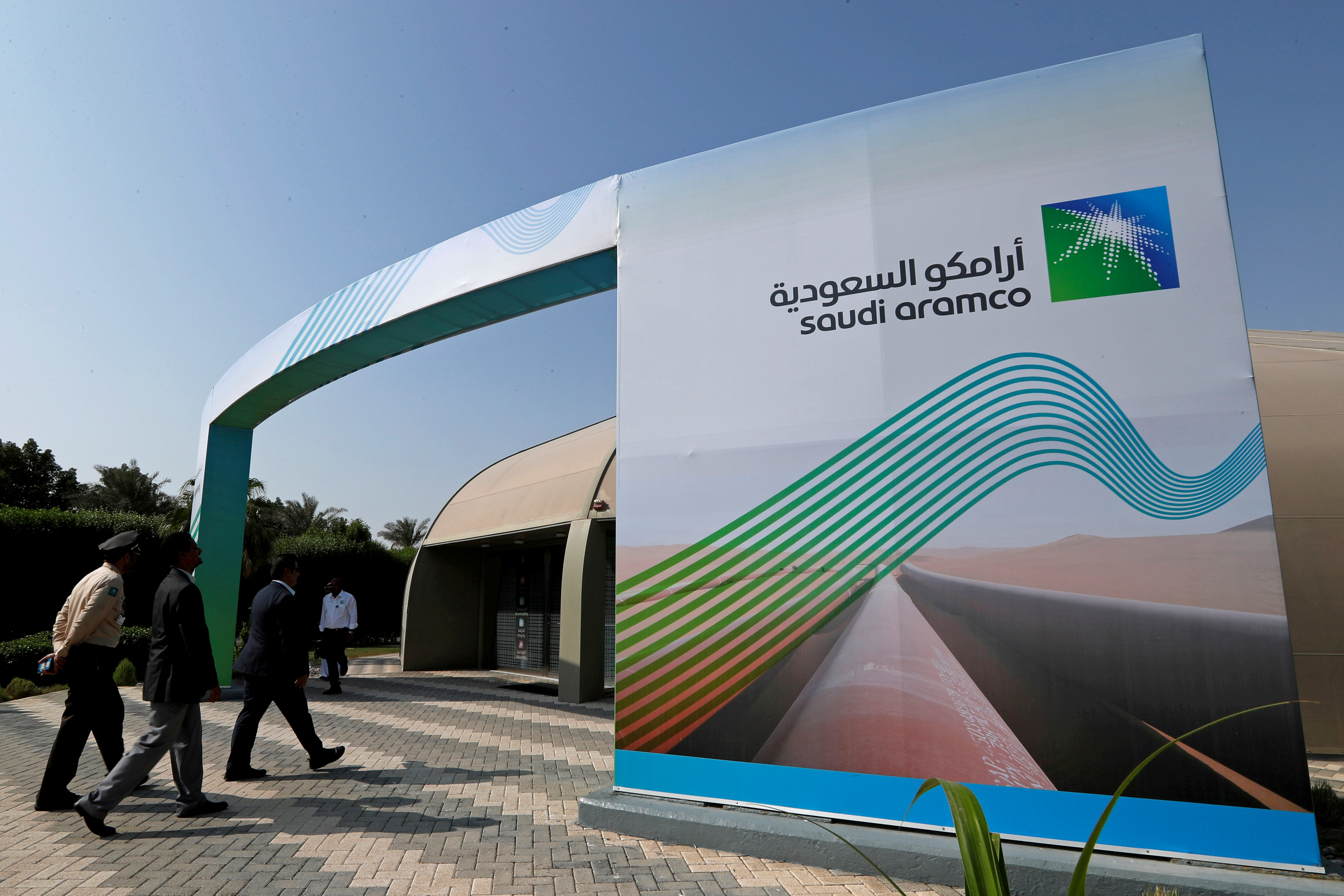 The logo of Aramco is seen as security personnel walk before the start of a press conference by Aramco at the Plaza Conference Center in Dhahran, Saudi Arabia November 3, 2019. REUTERS/Hamad I Mohammed