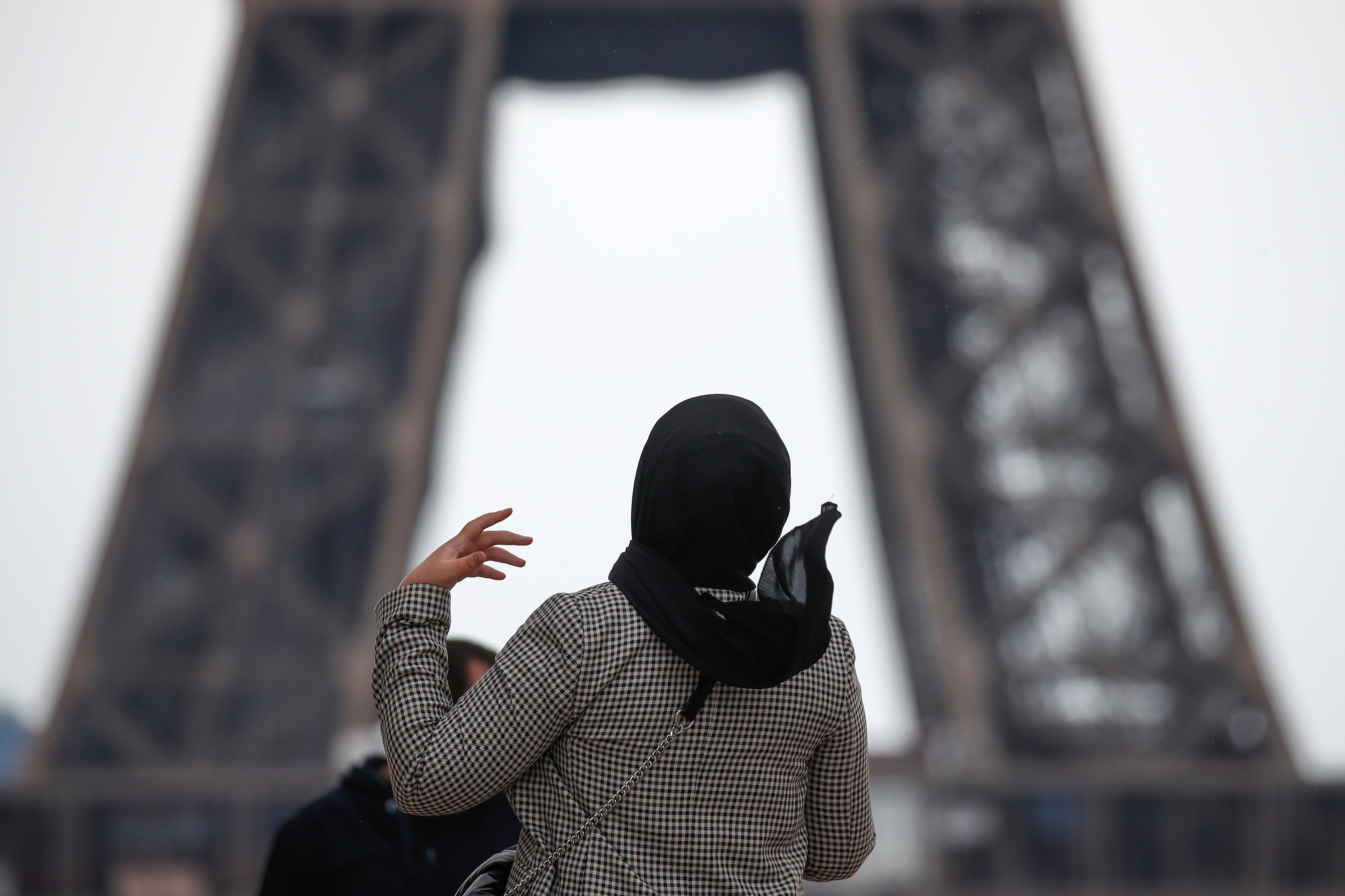 A woman wearing a hijab walks at Trocadero square near the Eiffel Tower in Paris, France, May 2, 2021. Picture taken on May 2, 2021. REUTERS/Gonzalo Fuentes