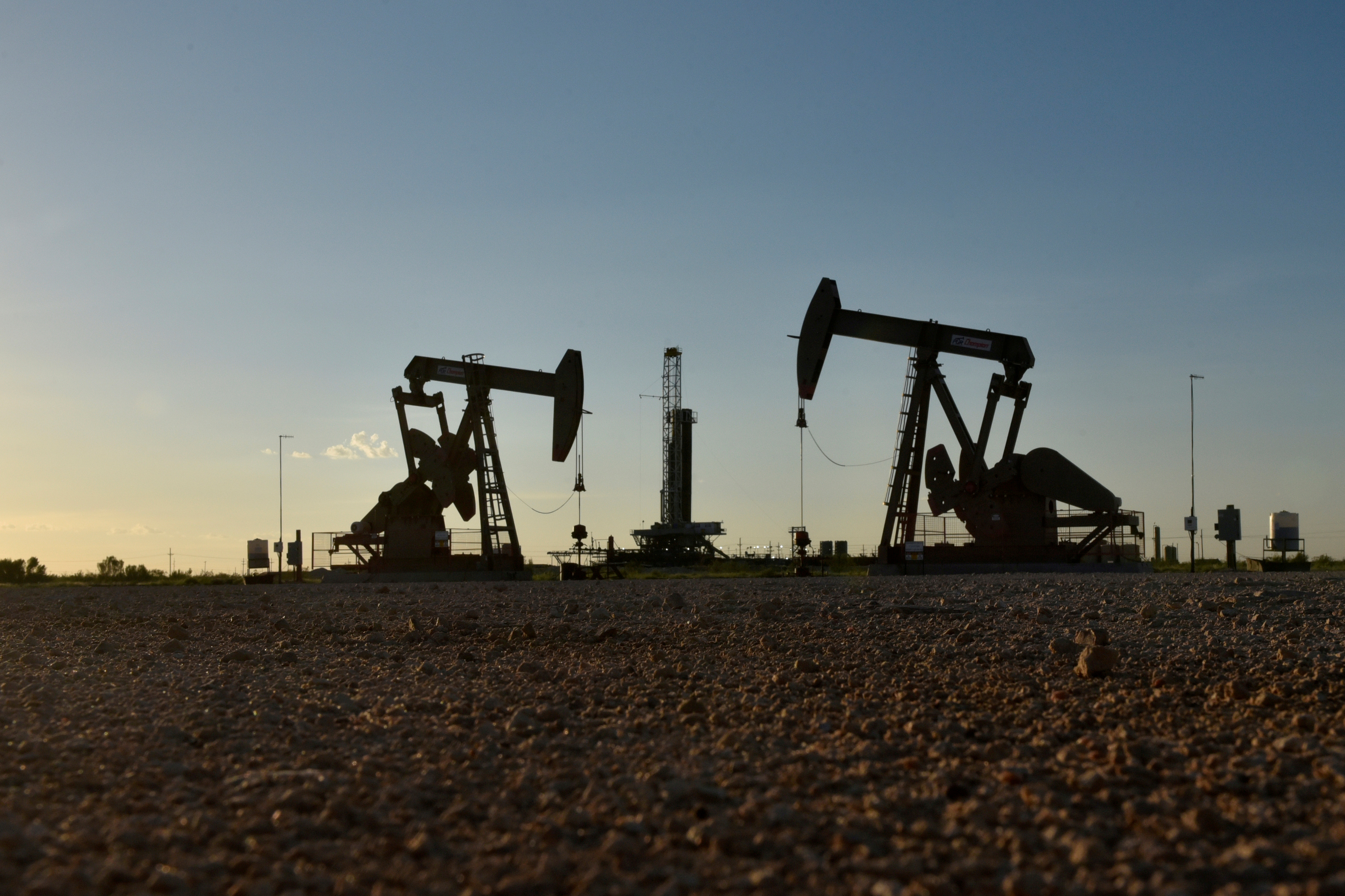 Pump jacks operate in front of a drilling rig in an oil field in Midland, Texas U.S. August 22, 2018. REUTERS/Nick Oxford/File Photo
