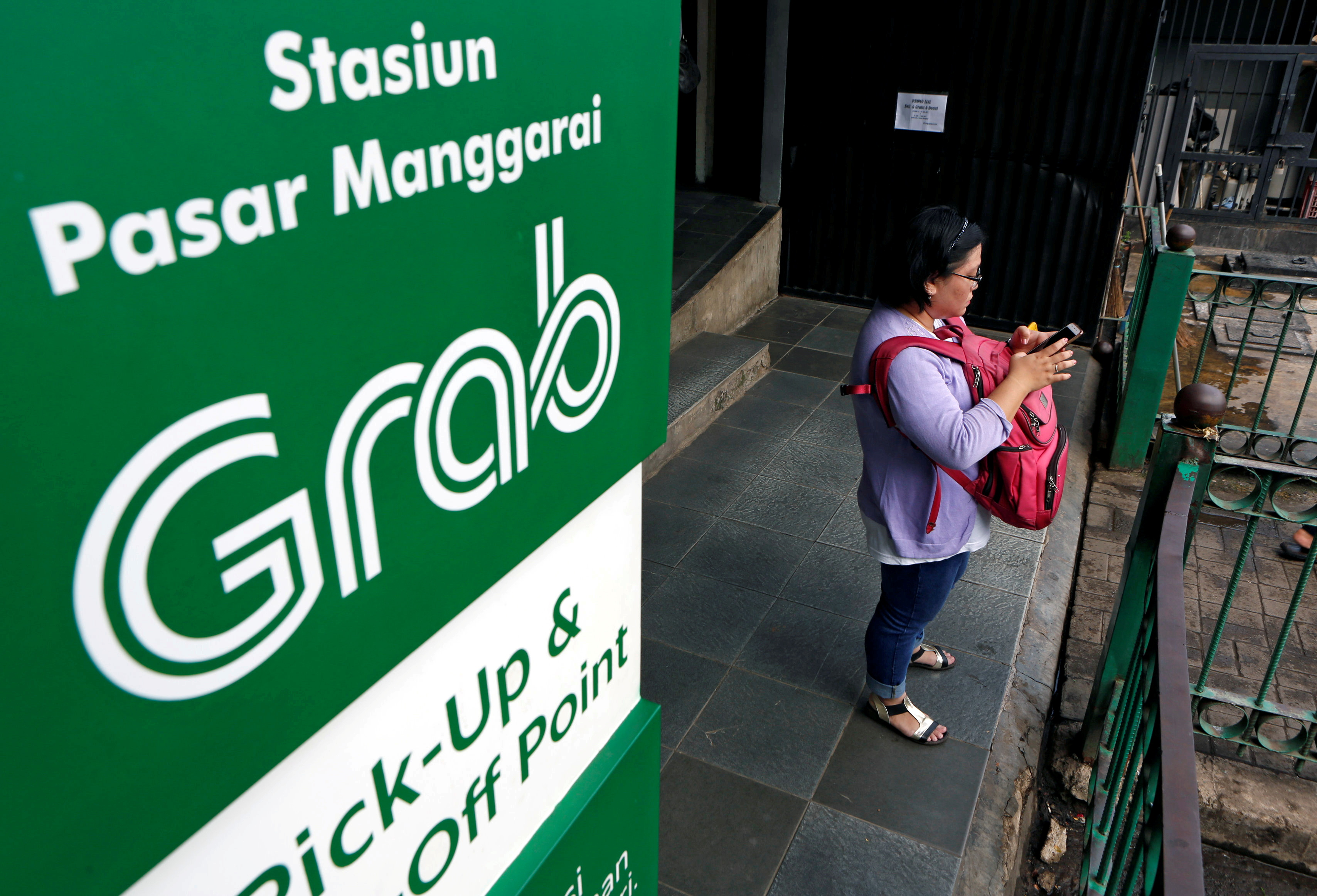 A woman uses her phone near a sign for the online ride-hailing service Grab at the Manggarai train station in Jakarta, Indonesia July 3, 2017. REUTERS/Agoes Rudianto/File Photo
