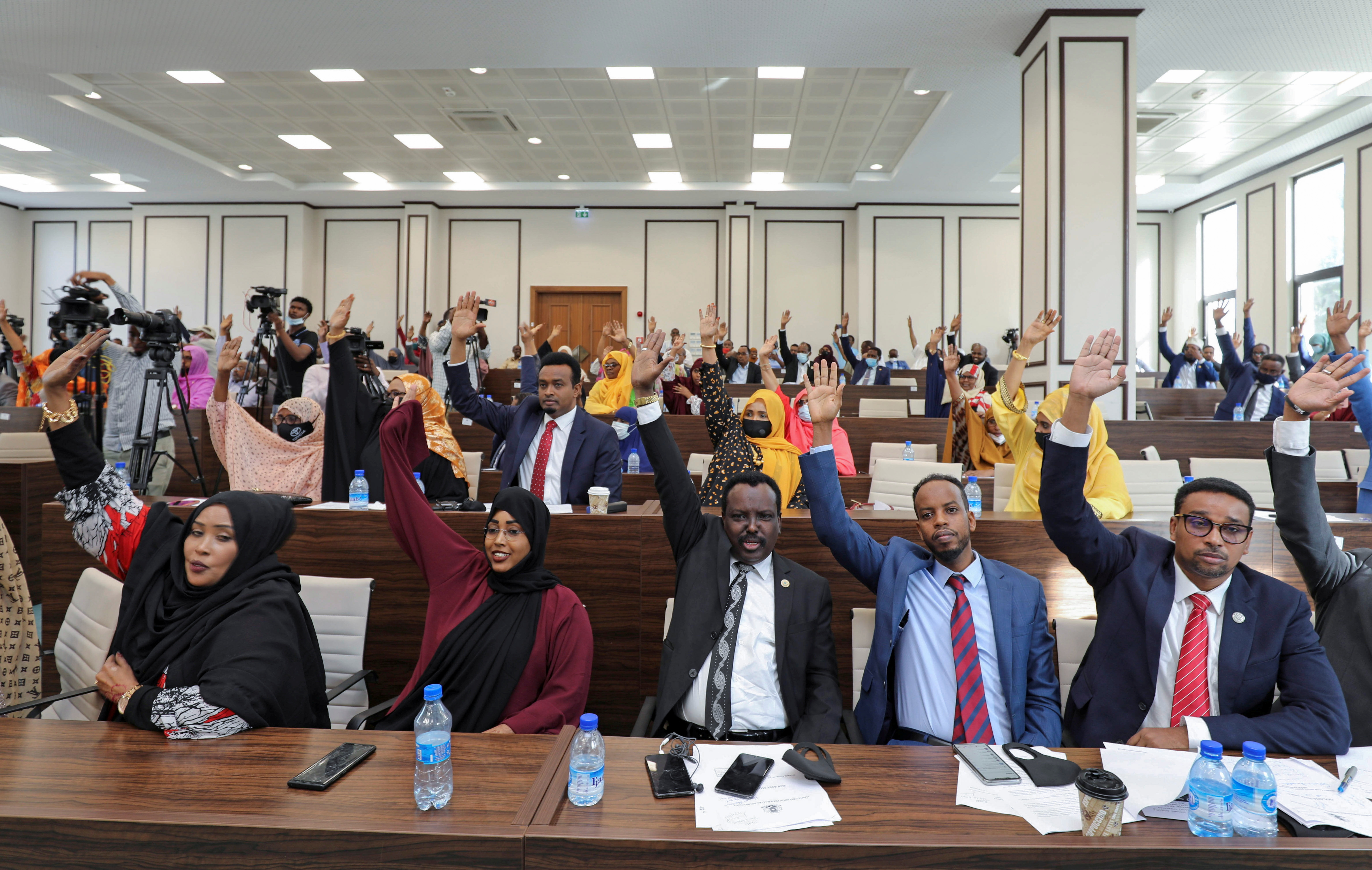 Somali legislators of the lower house of parliament raise their hands to vote to extend President Mohamed Abdullahi Mohamed's term for another two years to let the country prepare for direct elections, in Mogadishu, Somalia April 12, 2021. REUTERS/Feisal Omar