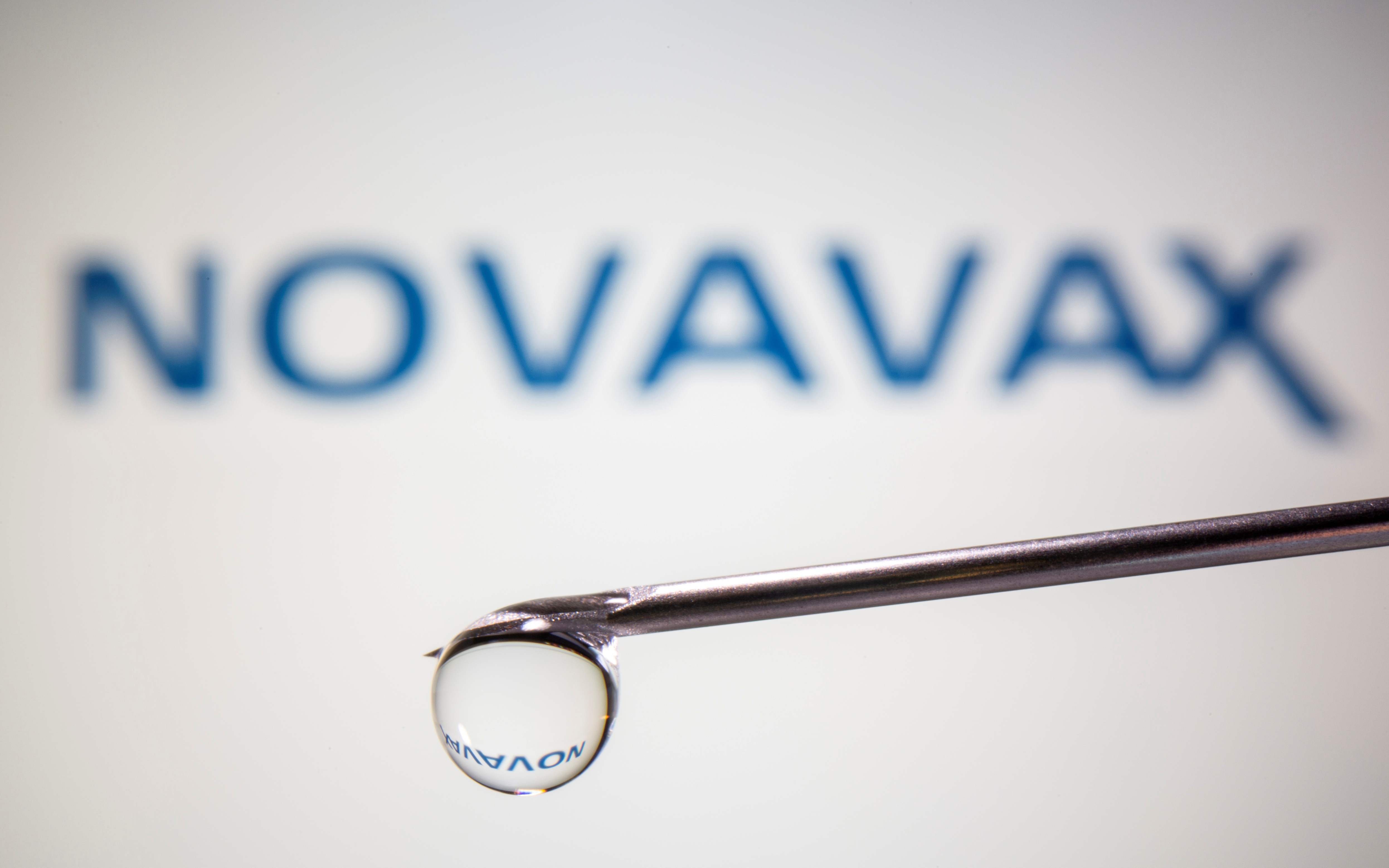 A Novavax logo is reflected in a drop on a syringe needle in this illustration taken November 9, 2020. REUTERS/Dado Ruvic/Illustration/File Photo