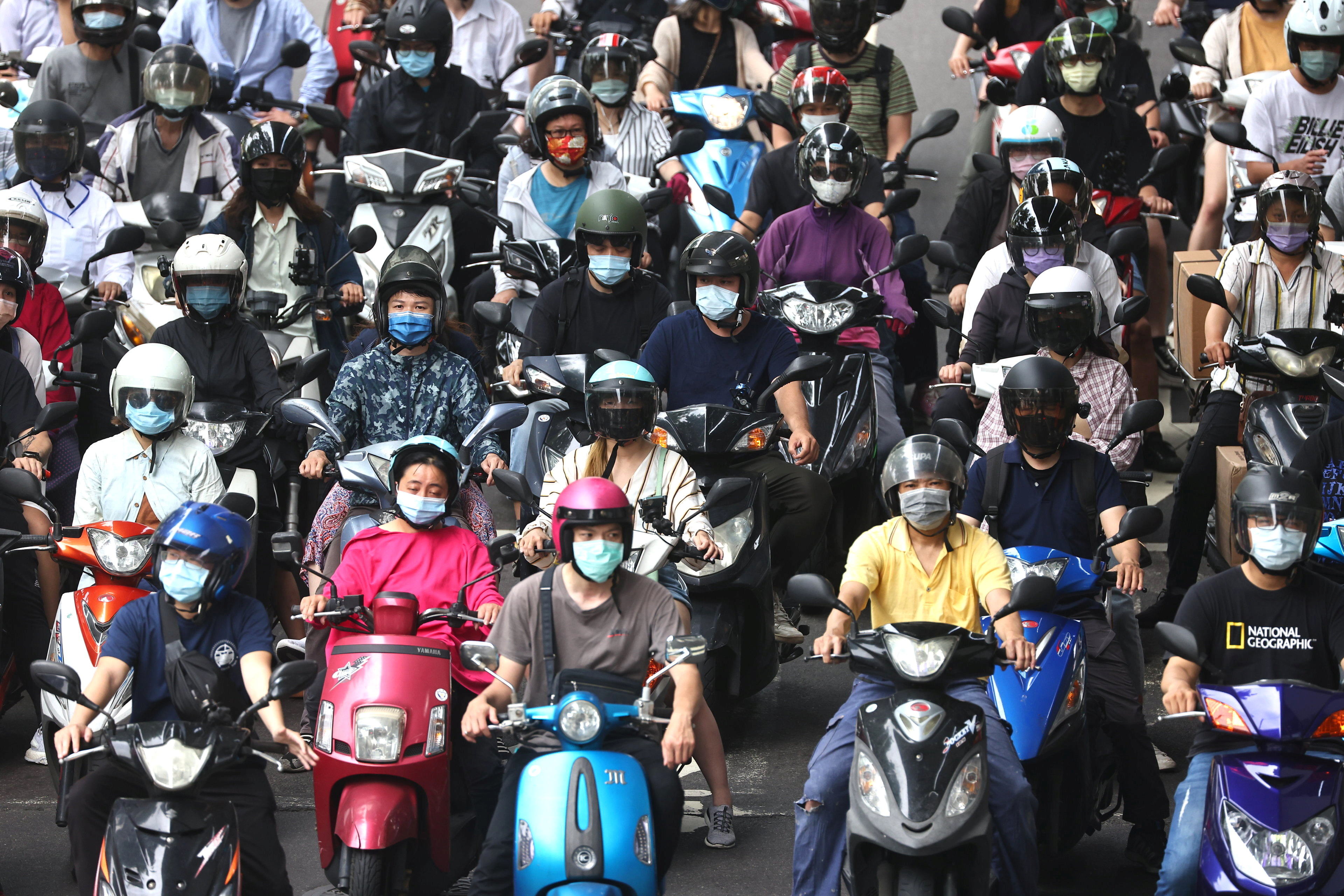 People riding motorcycles and wearing protective face masks wait at a traffic stop, amid a surge in coronavirus disease (COVID-19) infections in Taipei, Taiwan May 18, 2021. REUTERS/Ann Wang