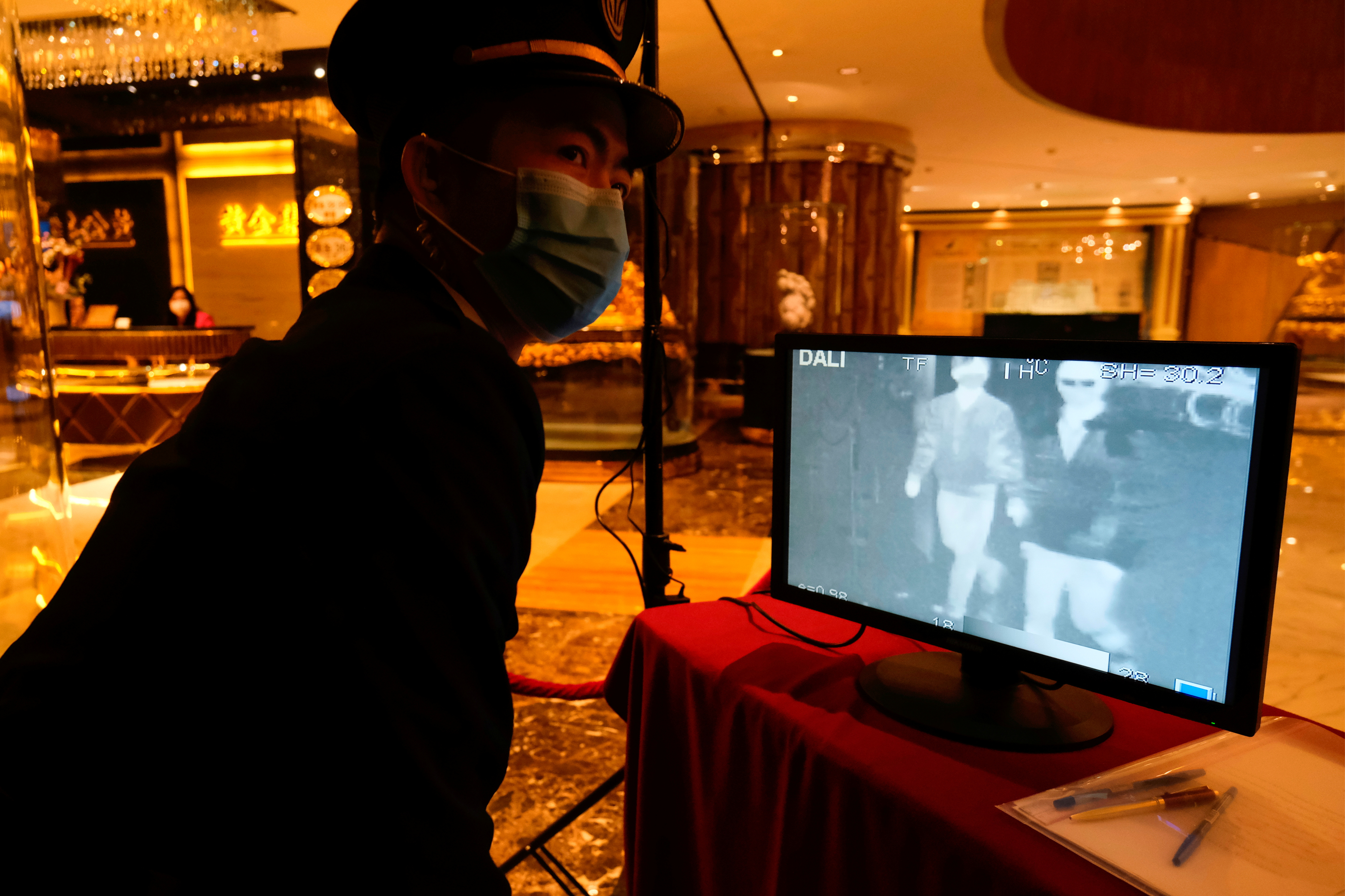 A security guard monitors thermal scanners that detect temperatures of visitors at the closed Grand Lisboa casino and hotel, following the coronavirus outbreak in Macau, China February 5, 2020. REUTERS/Tyrone Siu/File Photo