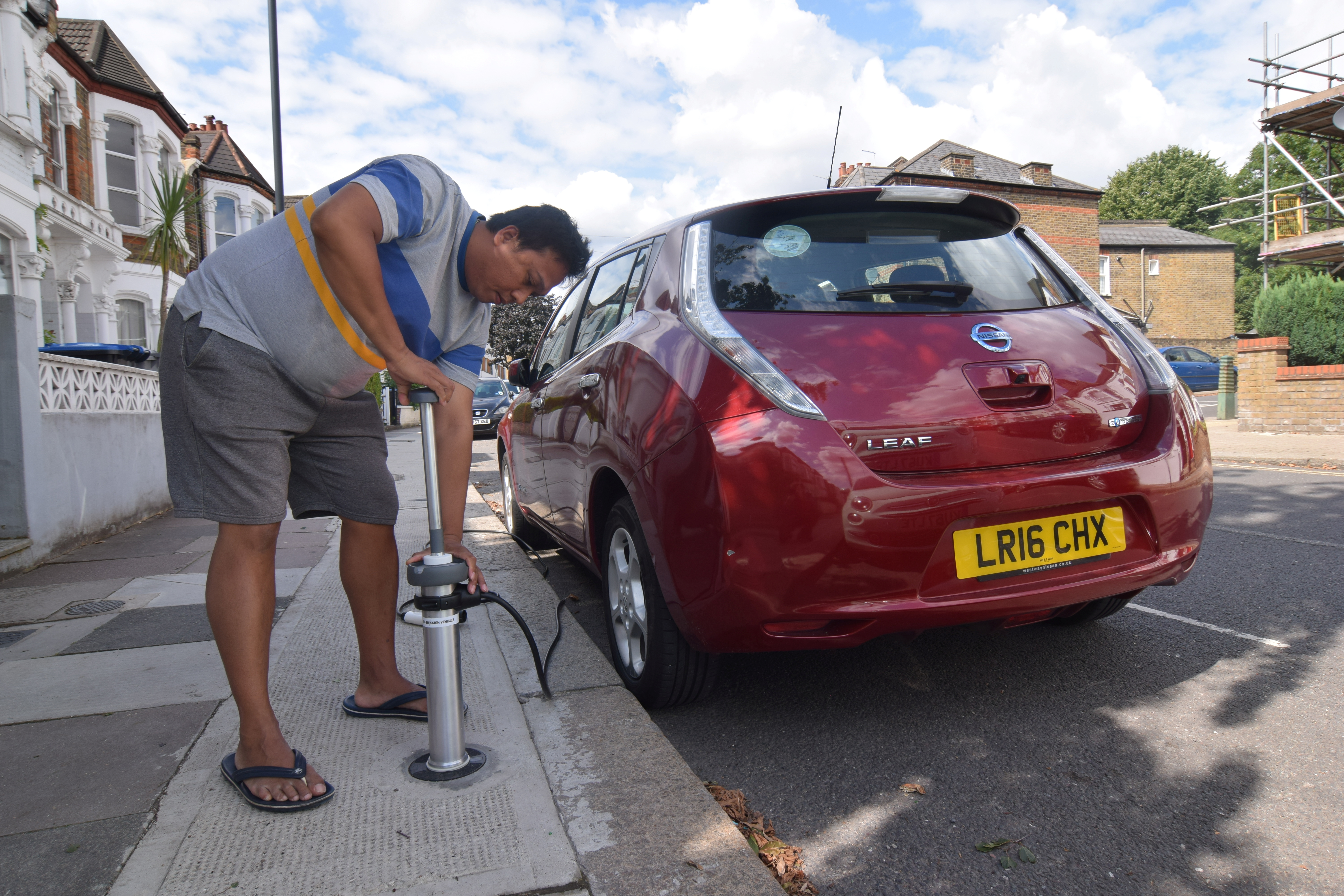 Uber driver Tim Win demonstrates plugging his fully-electric Nissan Leaf into an on-street residential electric vehicle charging system developed by startup Trojan Energy in London, Britain, August 2, 2021. REUTERS/Nick Carey