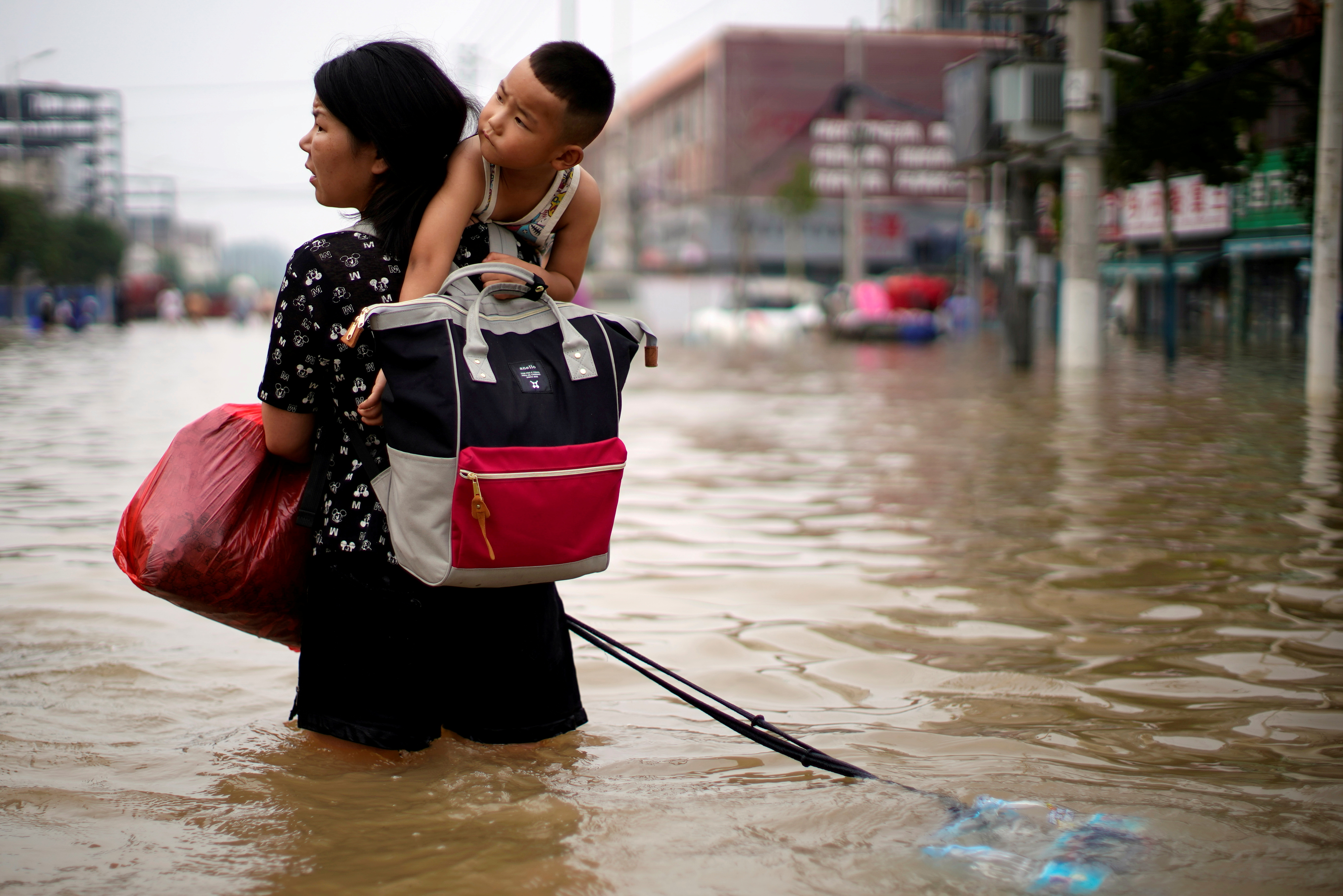 A woman carrying a child and belongings wades through floodwaters following heavy rainfall in Zhengzhou, Henan province, China July 23, 2021. REUTERS/Aly Song/File Photo
