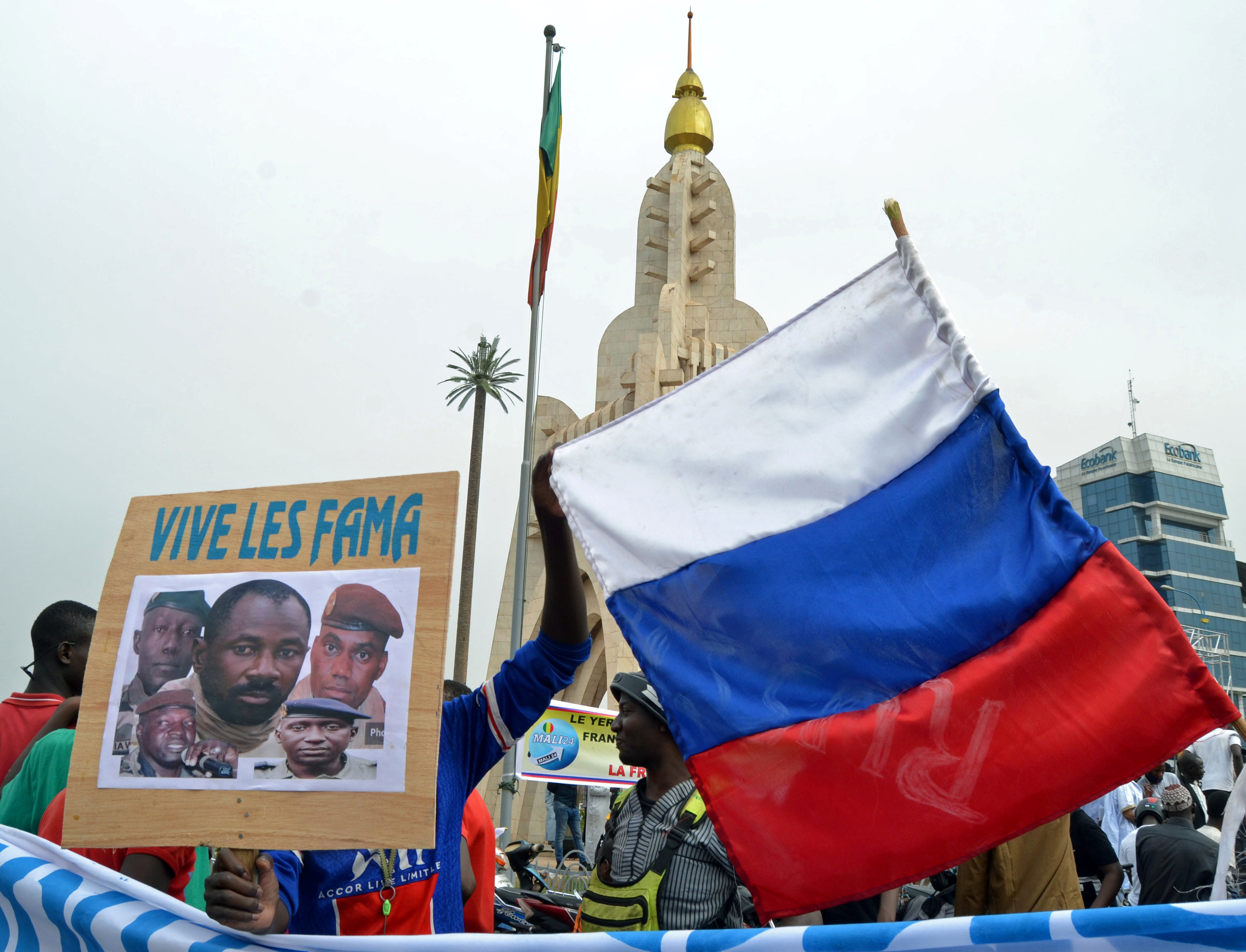 Malians holds a photograph with an image of coup leader Colonel Assimi Goita, who overthrew the president and prime minister, and Russia's flag during a pro-Malian Armed Forces (FAMA)  demonstratio.  REUTERS/ Amadou Keita