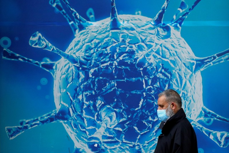 A man wearing a protective face mask walks past an illustration of a virus outside a regional science centre amid the coronavirus disease (COVID-19) outbreak, in Oldham, Britain August 3, 2020. REUTERS/Phil Noble/File Photo
