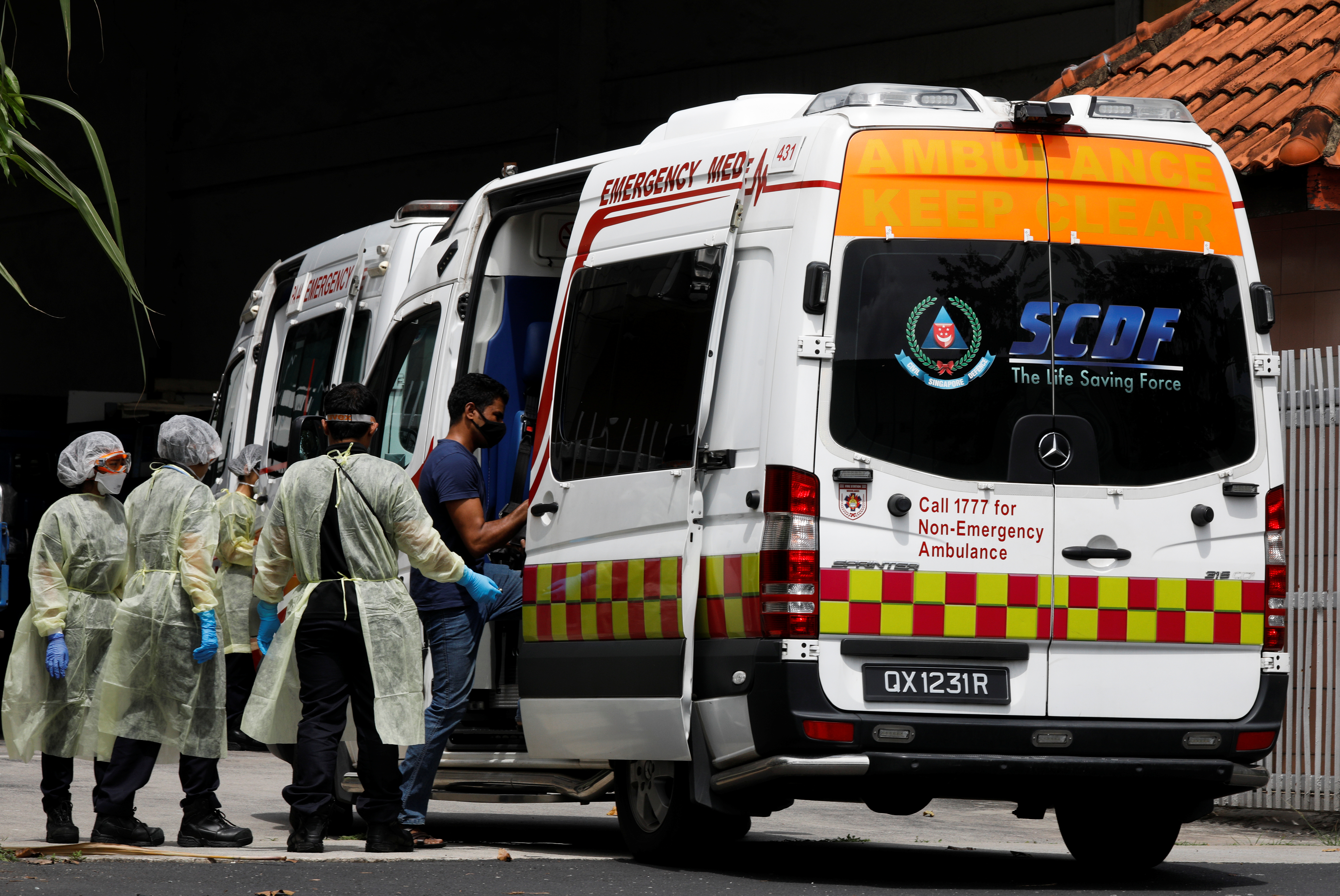 Medical personnel assist a migrant worker as he enters an ambulance at a factory-converted dormitory, amidst the coronavirus disease (COVID-19) outbreak in Singapore, April 28, 2020. REUTERS/Edgar Su