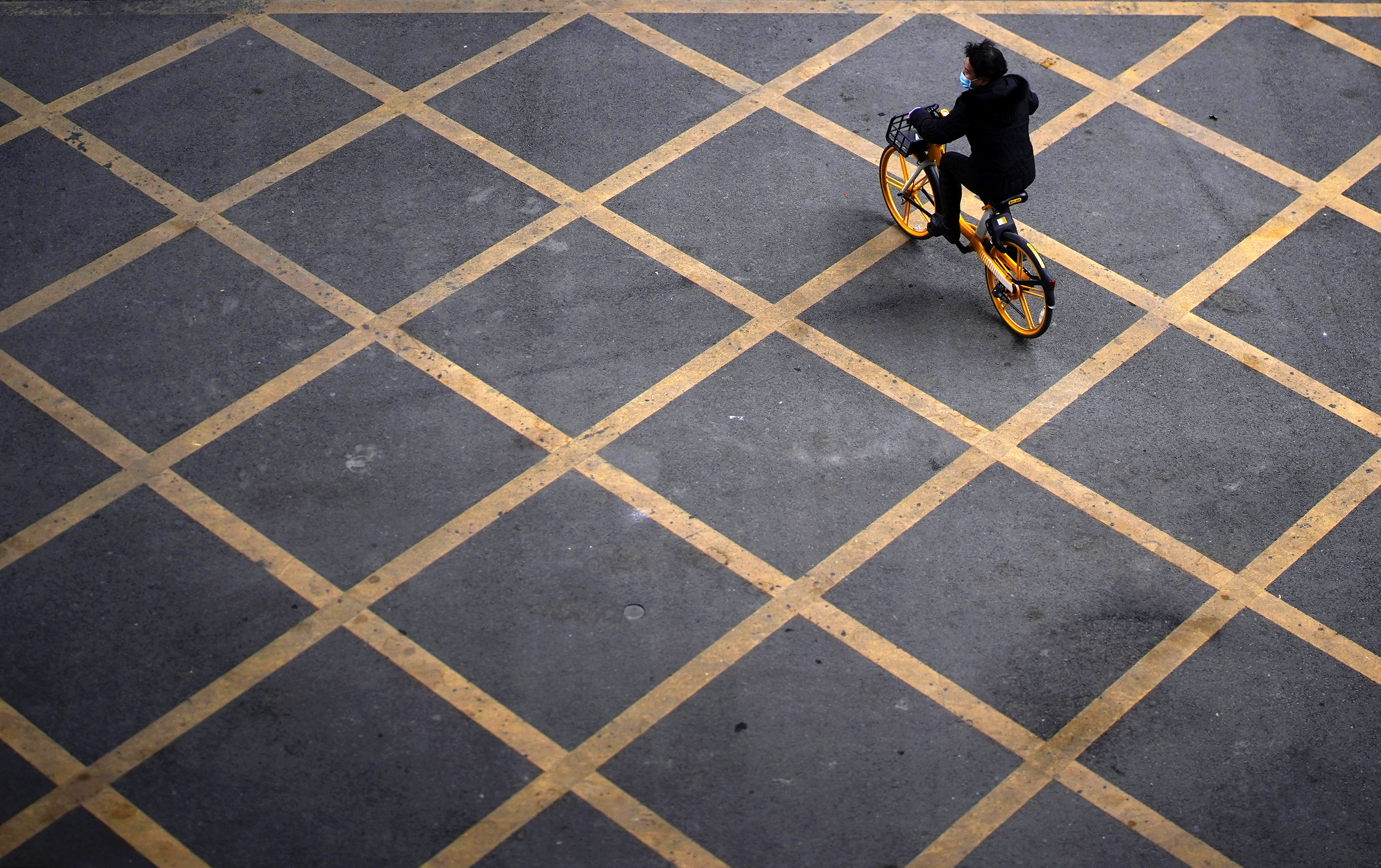 A person wearing a mask rides a bicycle of bike-sharing service on a street, almost a year after the start of the coronavirus disease (COVID-19) outbreak, in Wuhan, Hubei province, China December 17, 2020. REUTERS/Aly Song TPX IMAGES OF THE DAY