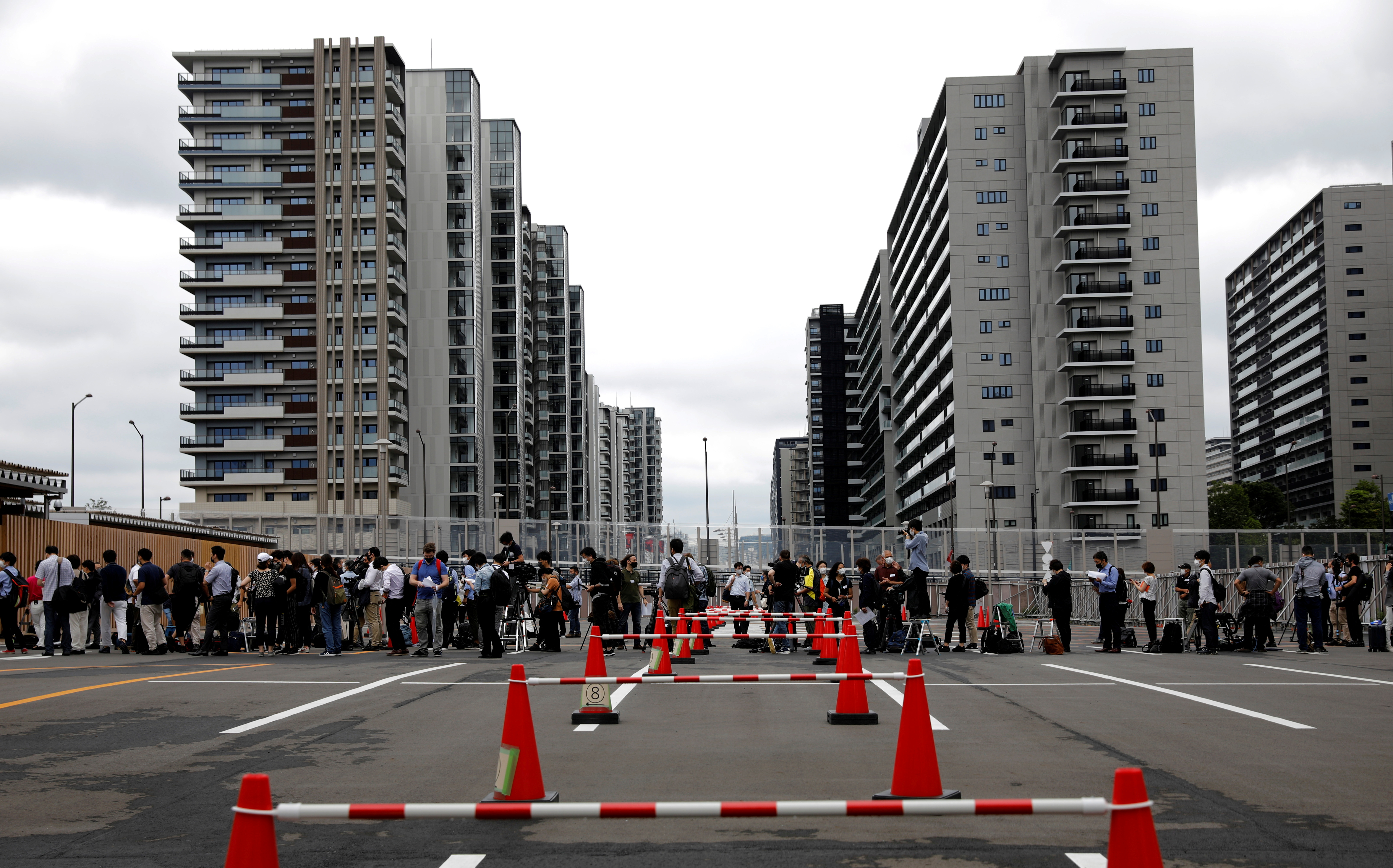Journalists stand in a line to enter the village plaza of the Tokyo 2020 Olympic and Paralympic Village for a press tour in Tokyo, Japan, June 20, 2021.   REUTERS/Kim Kyung-Hoon