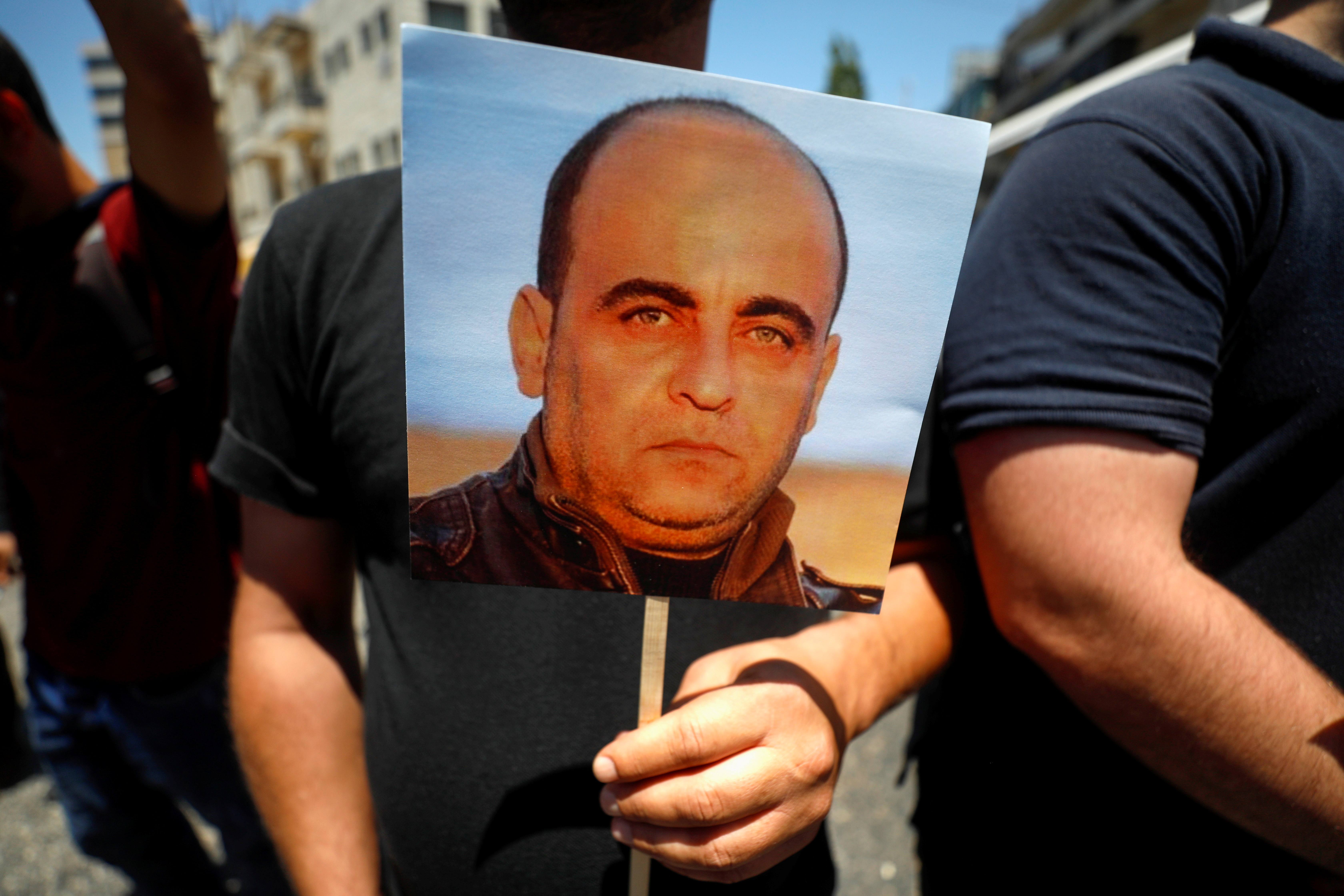 A demonstrator holds a picture of Nizar Banat, a Palestinian parliamentary candidate who criticised the Palestinian Authority and died after being arrested by PA security forces, during a protest in Ramallah in the Israeli-occupied West Bank, June 24, 2021. REUTERS/Mohamad Torokman