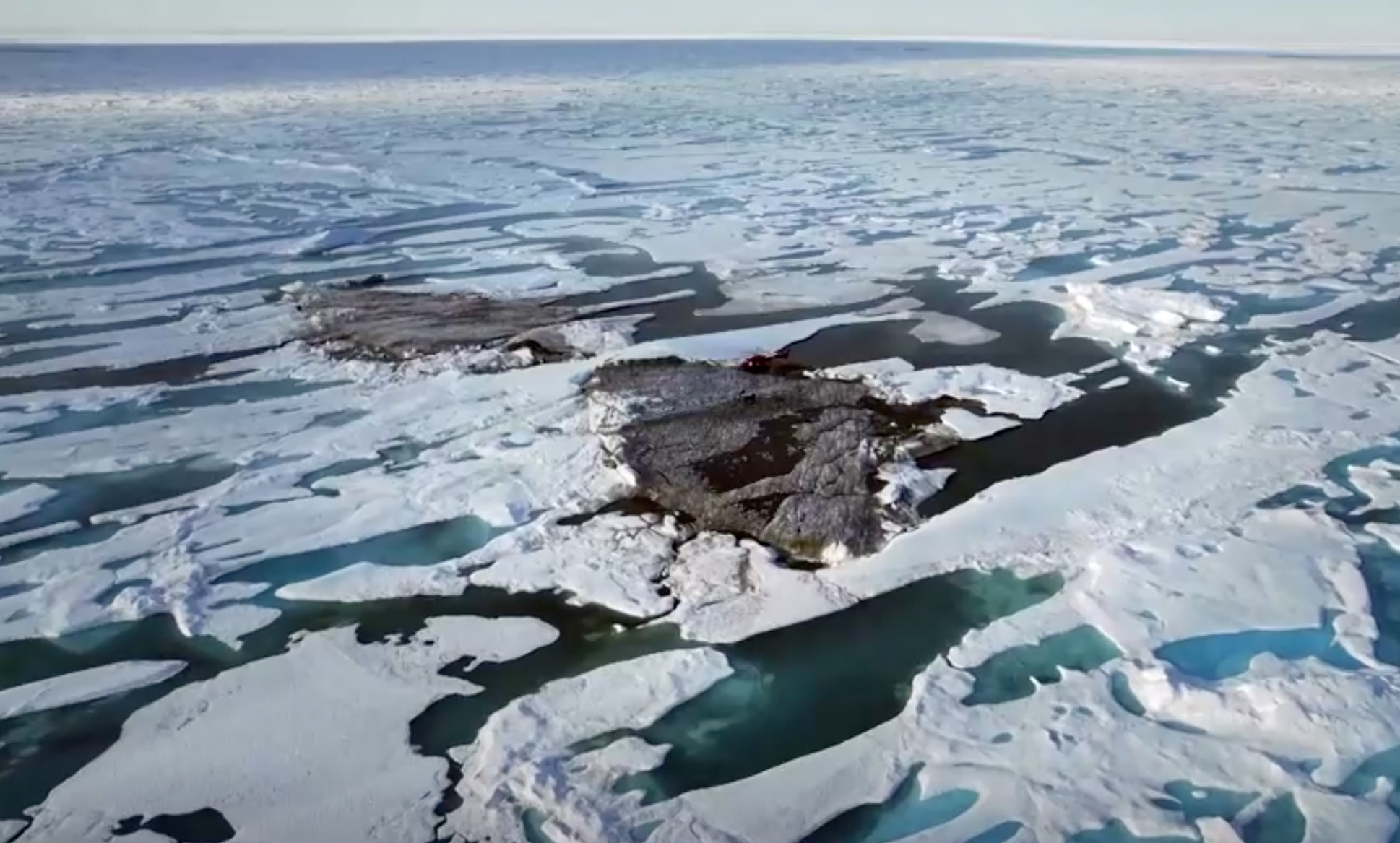 An aerial view of a tiny island off the coast of Greenland revealed by shifting pack ice.    JULIAN CHARRIERE/via REUTERS TV