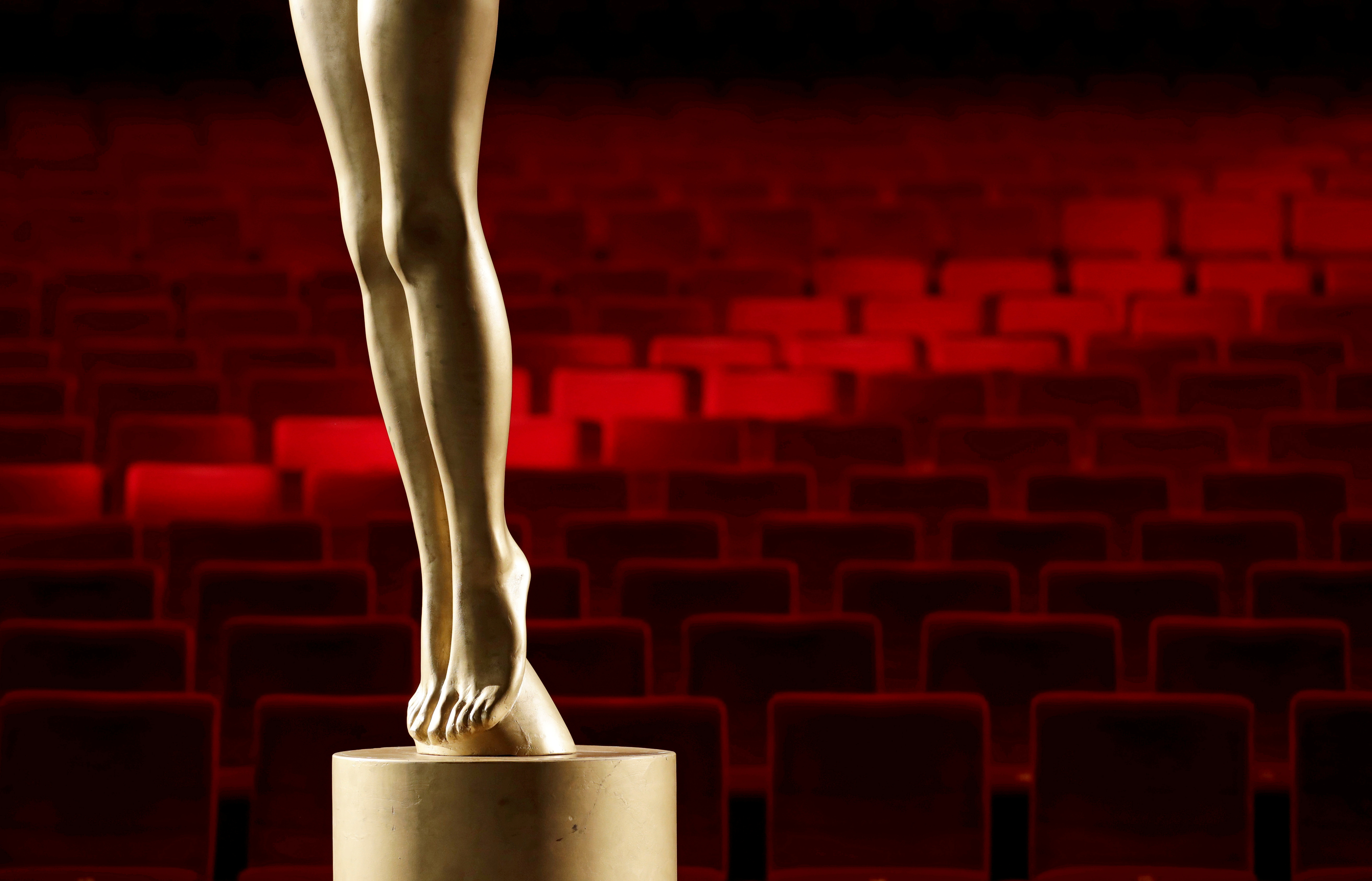 Empty seats are seen behind a statue of the Crystal Globe Award inside a cinema before a broadcast of an opening ceremony, as the Karlovy Vary International Film Festival launches a nationwide programme to bring its films to cinemas around the country after cancelling its main events following the coronavirus disease (COVID-19) outbreak in Karlovy Vary, Czech Republic, July 3, 2020.  REUTERS/David W Cerny