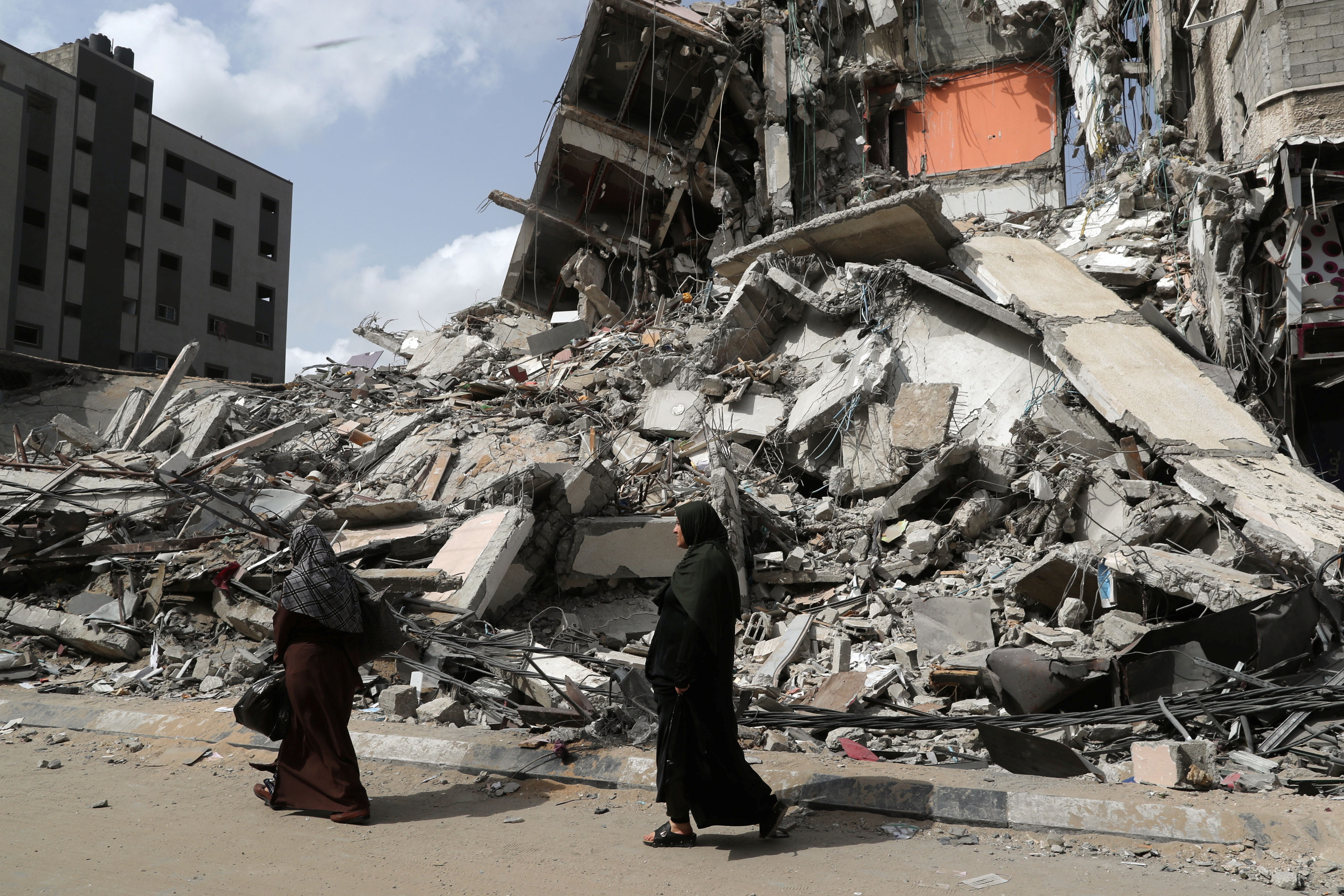 Palestinians walk past the ruins of a building destroyed in an Israeli air strike in the recent cross-border violence between Palestinian militants and Israel, in Gaza May 21, 2021. REUTERS/Suhaib Salem