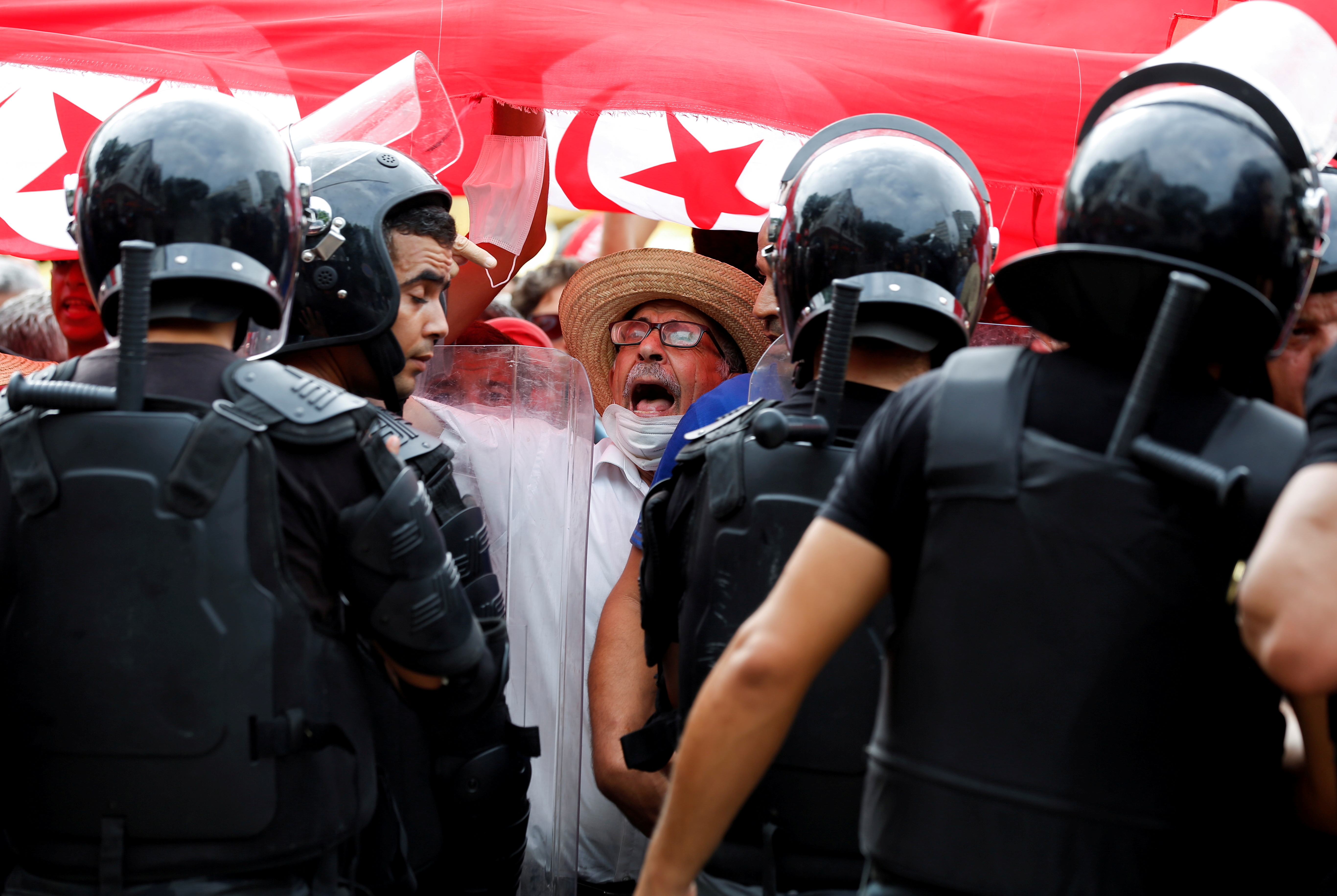 A demonstrator shouts slogans near police officers standing guard during a protest against Tunisian President Kais Saied's seizure of governing powers, in Tunis, Tunisia, September 26, 2021. REUTERS/Zoubeir Souissi