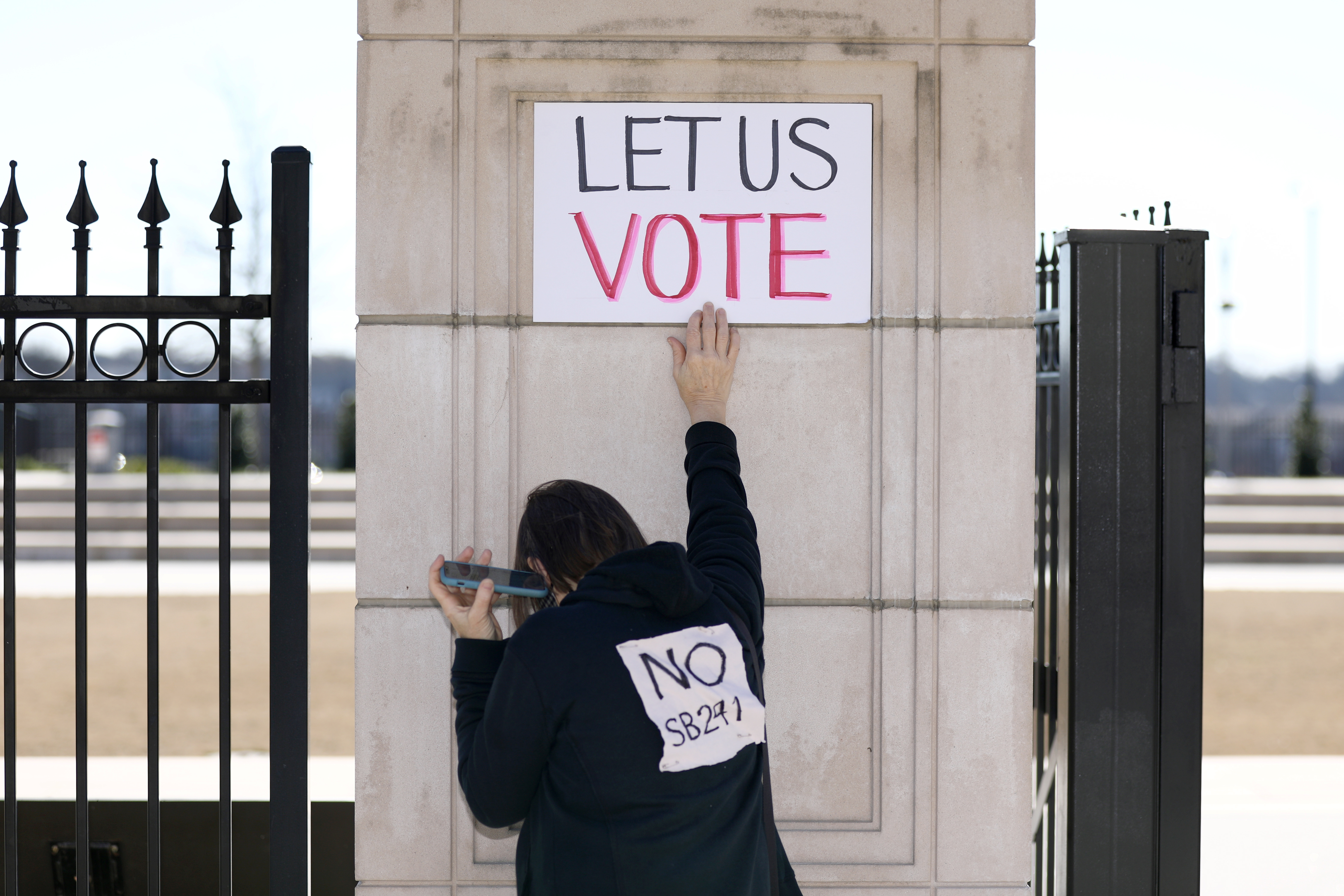 A protester attends a gathering outside of the Georgia State Capitol to protest HB 531, which would place tougher restrictions on voting in Georgia, in Atlanta, Georgia, U.S. March 4, 2021. REUTERS/Dustin Chambers