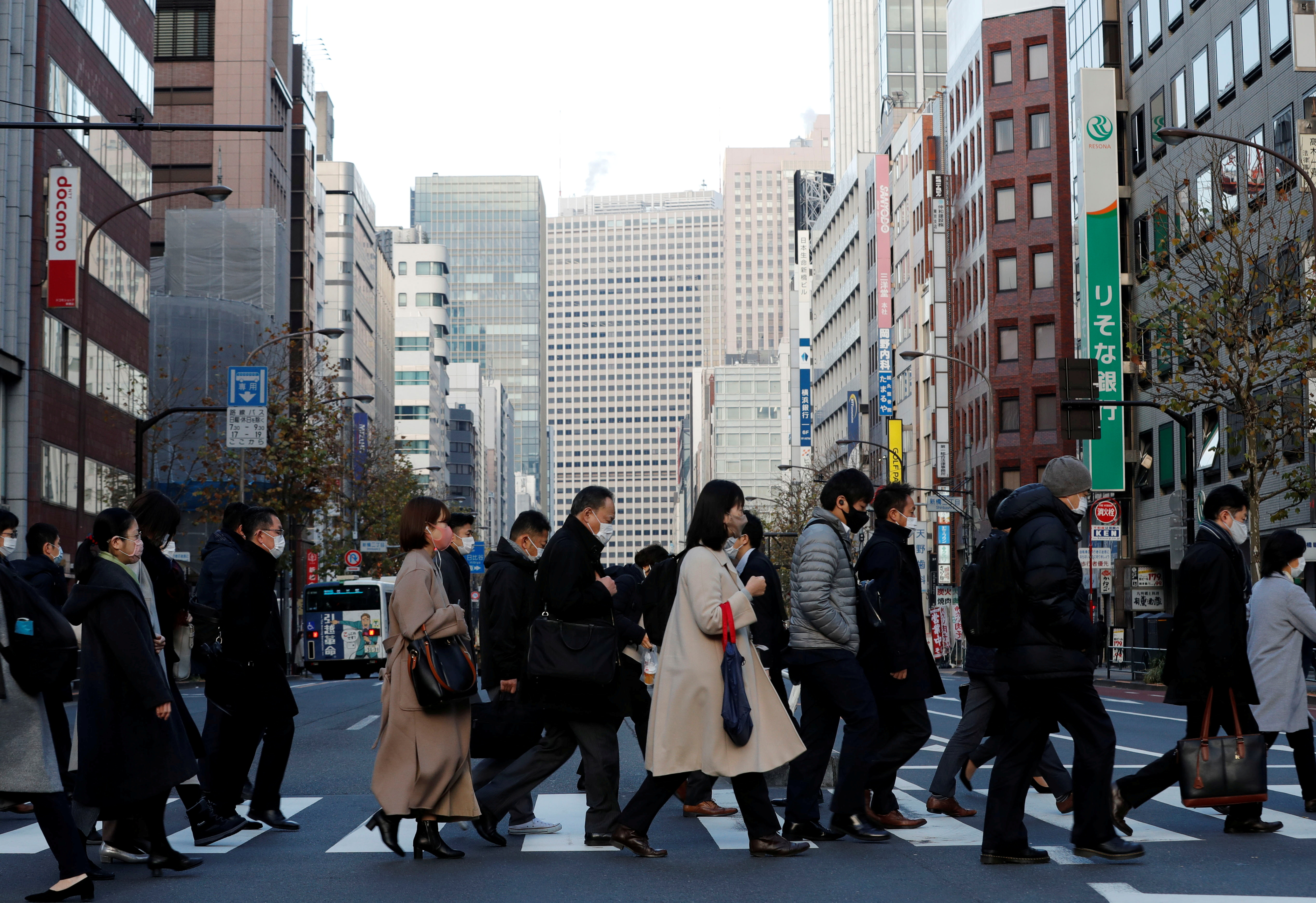 Pedestrians wearing protective masks, following the coronavirus disease (COVID-19) outbreak, make their way during commuting hour at a business district in Tokyo, Japan, January 7, 2021. REUTERS/Kim Kyung-Hoon/File Photo
