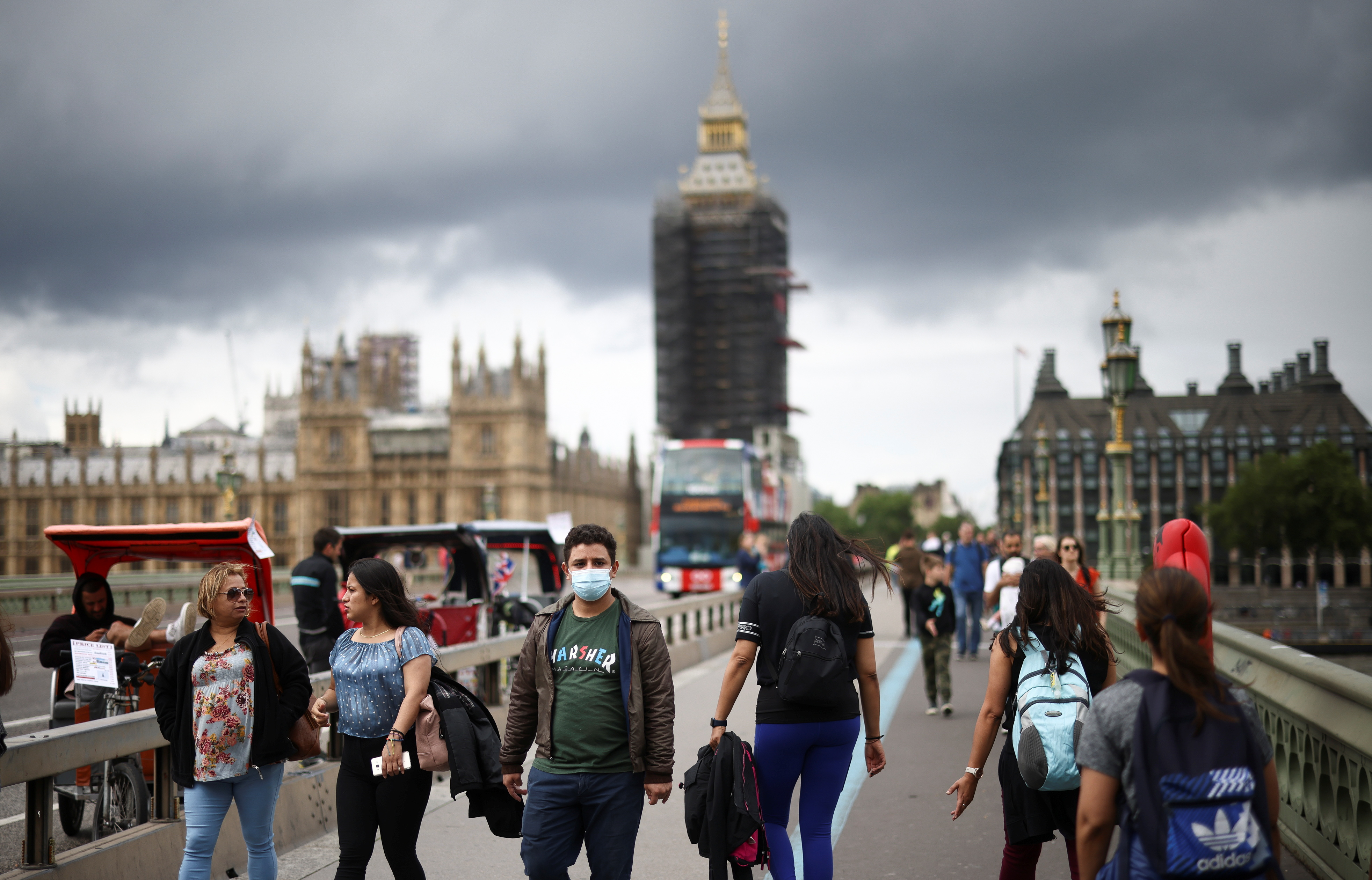 People, some wearing protective face masks, walk over Westminster Bridge, amid the coronavirus disease (COVID-19) pandemic, in London, Britain, July 4, 2021. REUTERS/Henry Nicholls