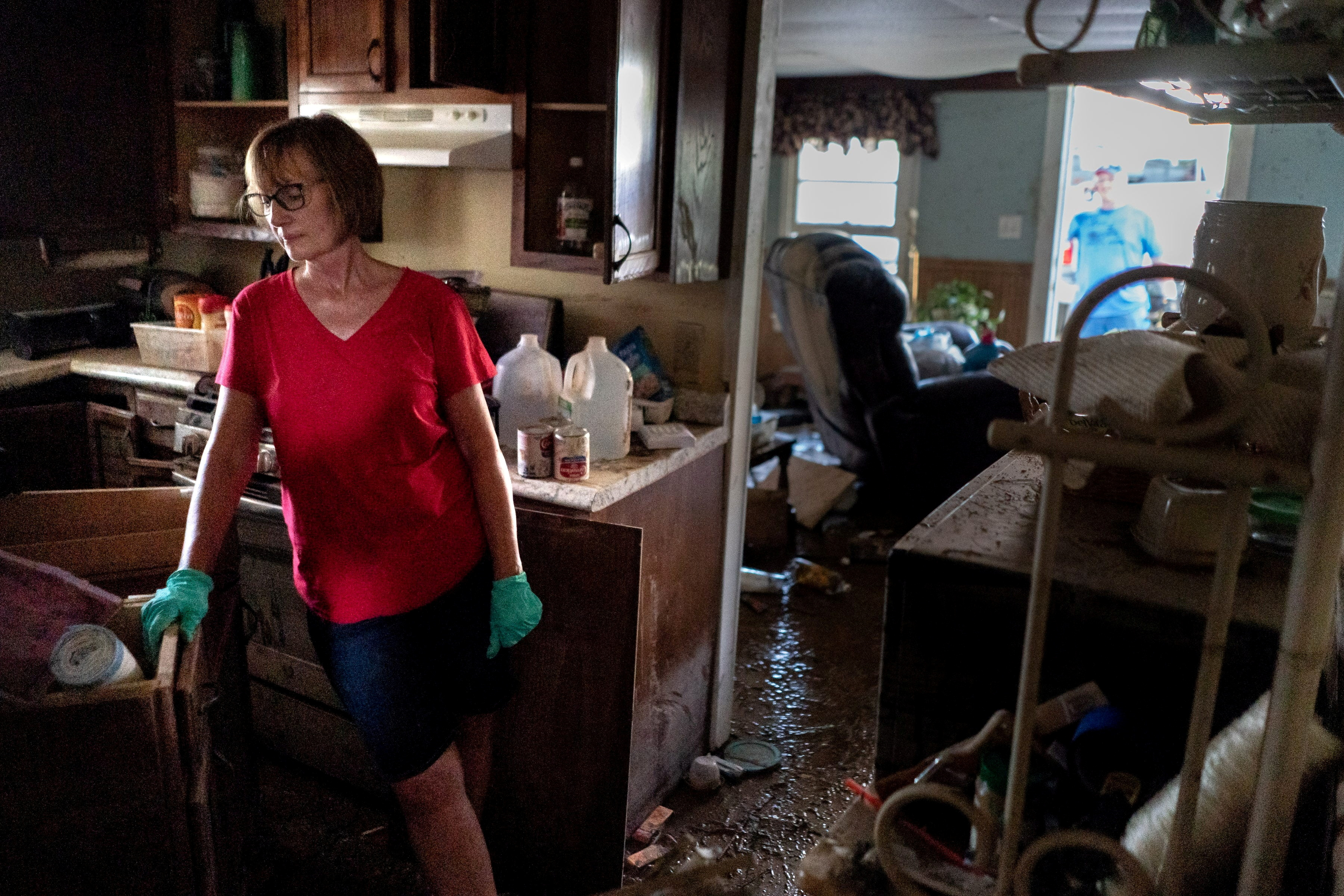 Jaquita Buchanan works on salvaging items from her mother's home after flooding in Waverly, Tennessee, U.S., August 23, 2021. Picture taken August 23, 2021. Her mother escaped from the home safely, but her step-father died while assisting a neighbor. Andrew Nelles/The Tennessean/USA Today via REUTERS