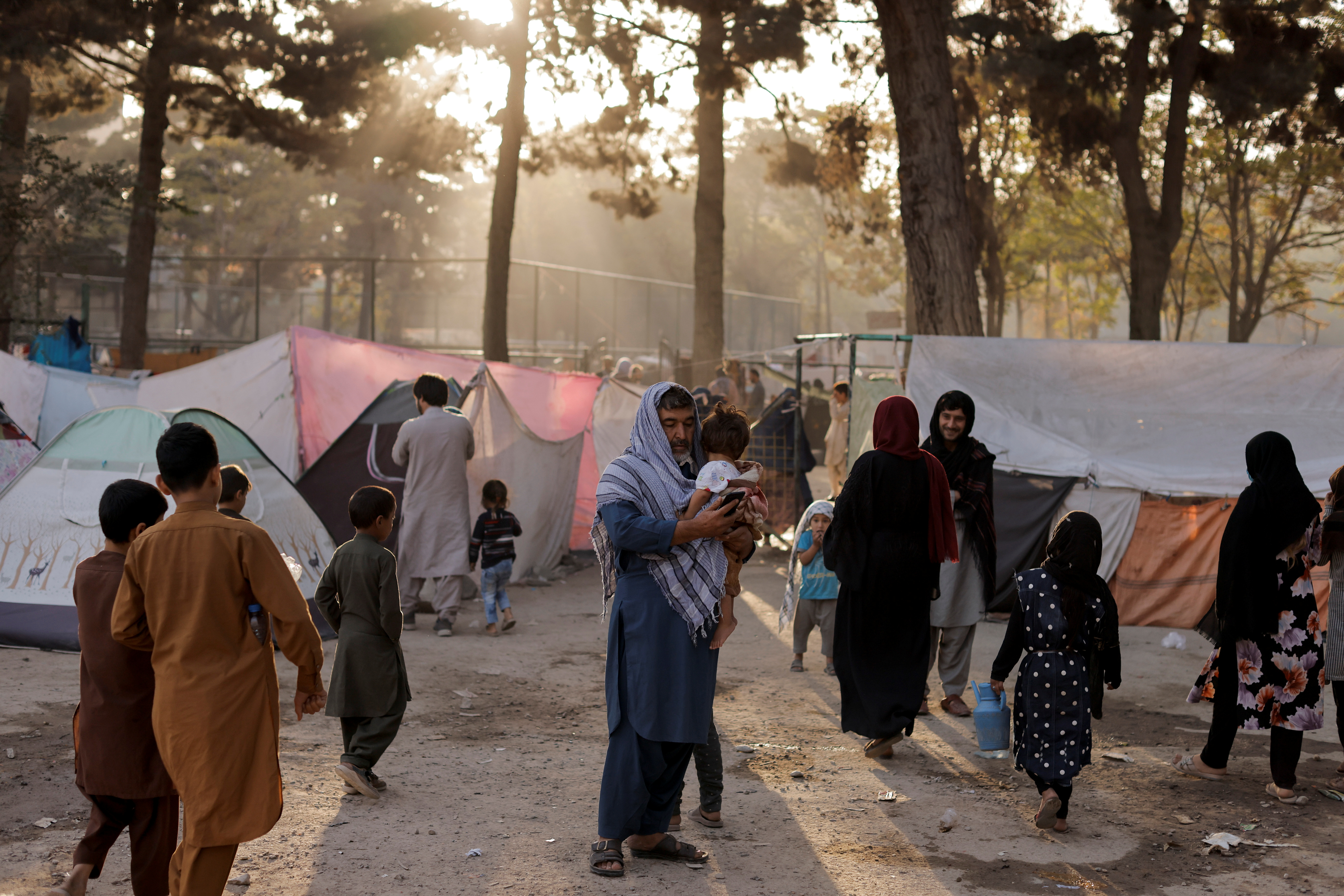 Displaced Afghan families, who flee the violence in their provinces, stand near tents in a makeshift shelter at Shahr-e Naw park, in Kabul, Afghanistan October 4, 2021. REUTERS/Jorge Silva
