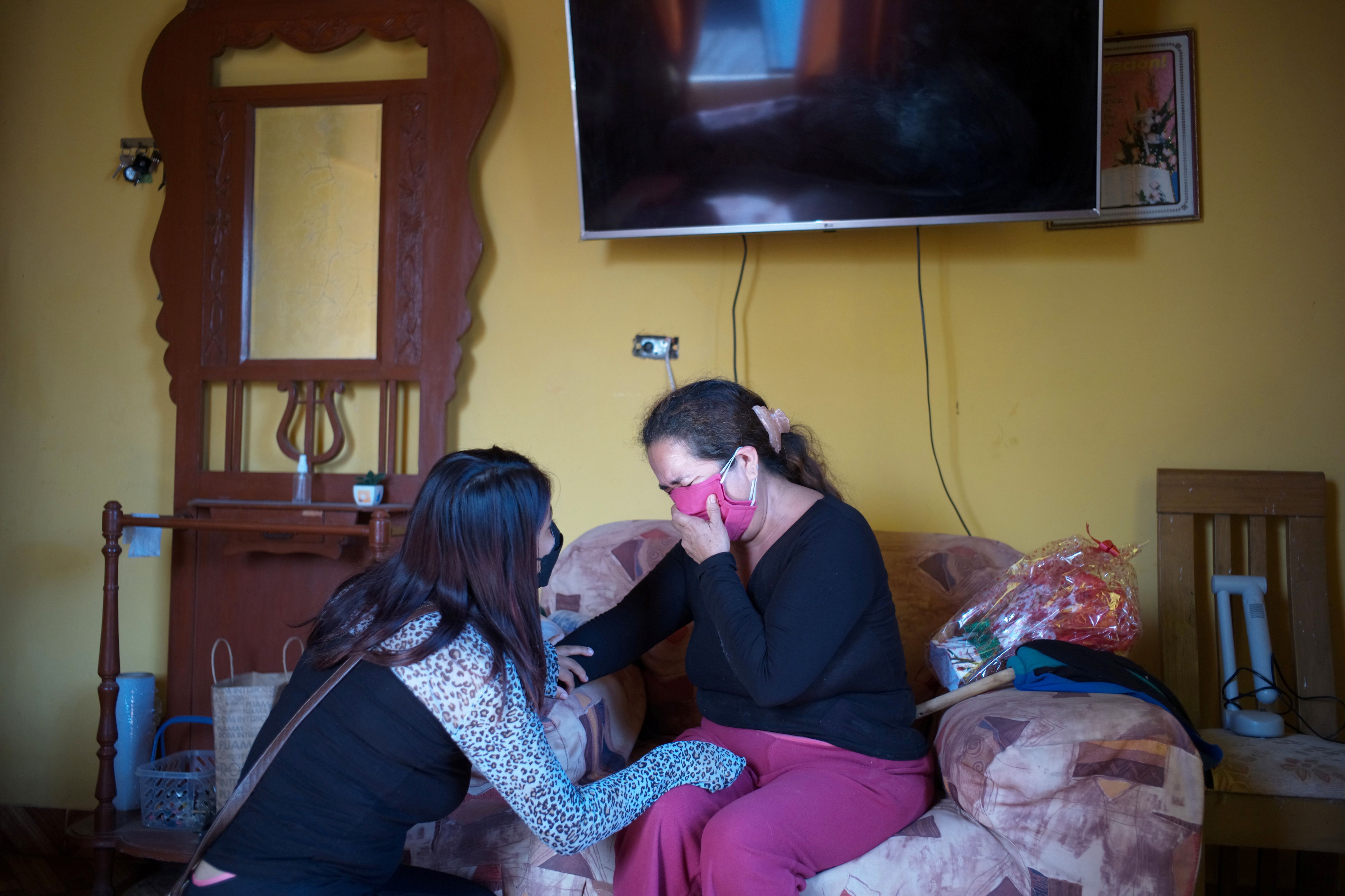 Hellen Nanez, who lost 13 relatives to the coronavirus disease (COVID-19) and whose father Guillermo Alejandro Nanez is being treated for COVID-19 in the Intensive Care Unit, comforts her aunt Paulina Nanez after telling her that Guillermo's conditions has worsened, in Pisco, Peru, May 10, 2021. REUTERS/Alessandro Cinque