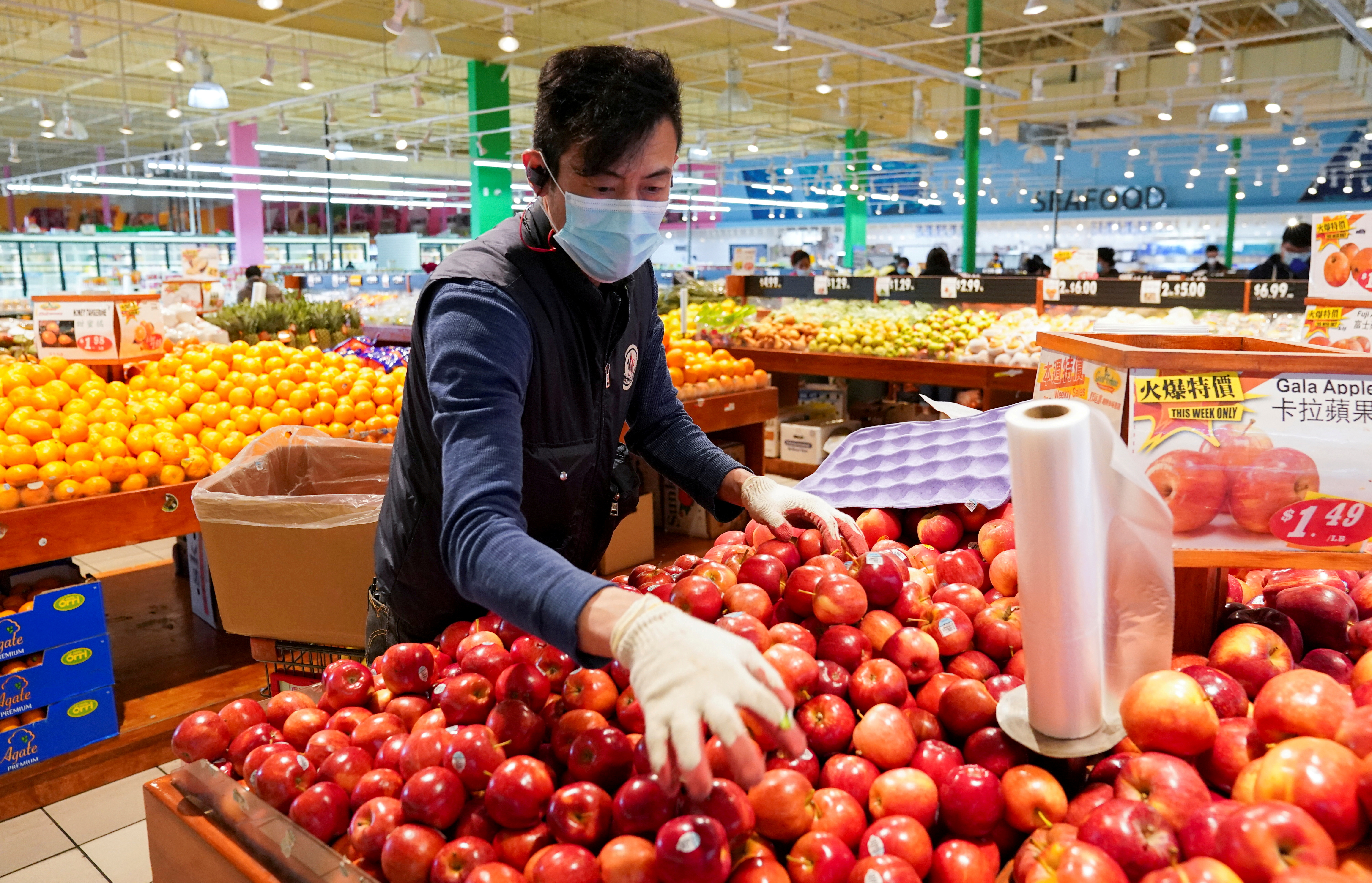 Wearing a mask and gloves, a worker re-stocks apples in an Asian grocery store in Falls Church, Virginia, U.S., April 3, 2020. REUTERS/Kevin Lamarque