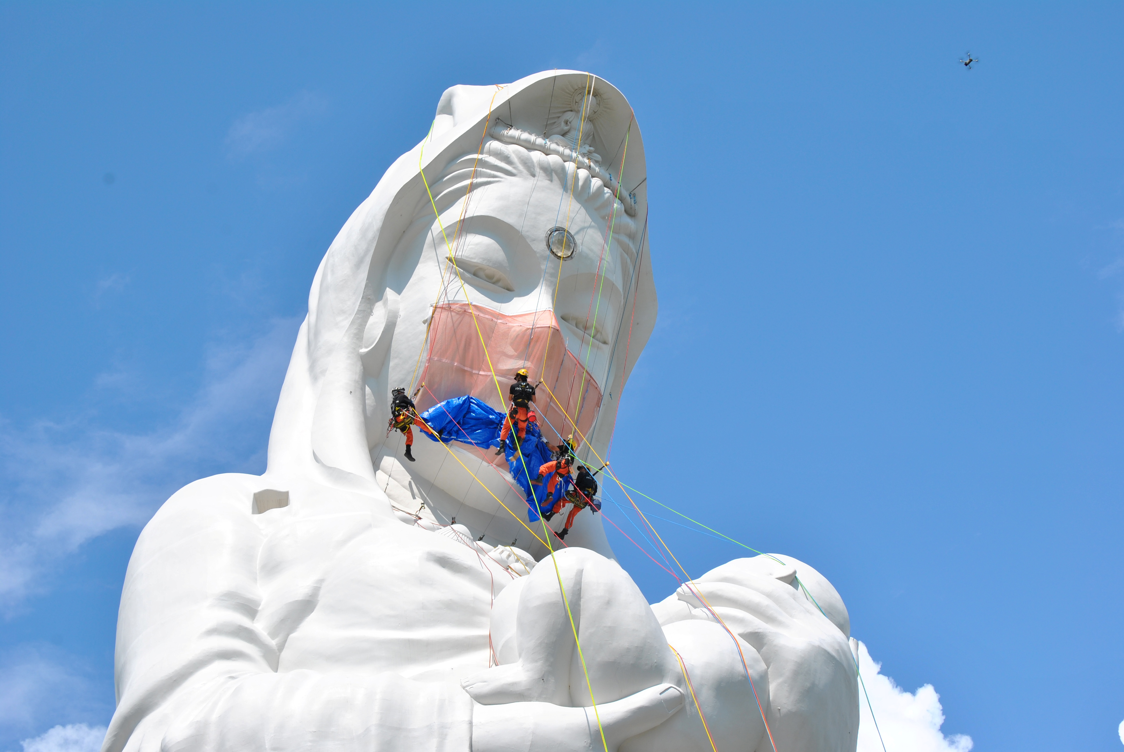 Workers place a mask on a 57-metre-high statue of Buddhist goddess Kannon to pray for the end of the coronavirus disease (COVID-19) pandemic at Houkokuji Aizu Betsuin temple in Aizuwakamatsu, Fukushima Prefecture, Japan in this handout photo taken on June 15 2021. Picture taken on June 15, 2021. Houkokuji Aizu Betsuin/Handout via REUTERS   ATTENTION EDITORS - THIS IMAGE HAS BEEN SUPPLIED BY A THIRD PARTY. NO RESALES. NO ARCHIVES. MANDATORY CREDIT