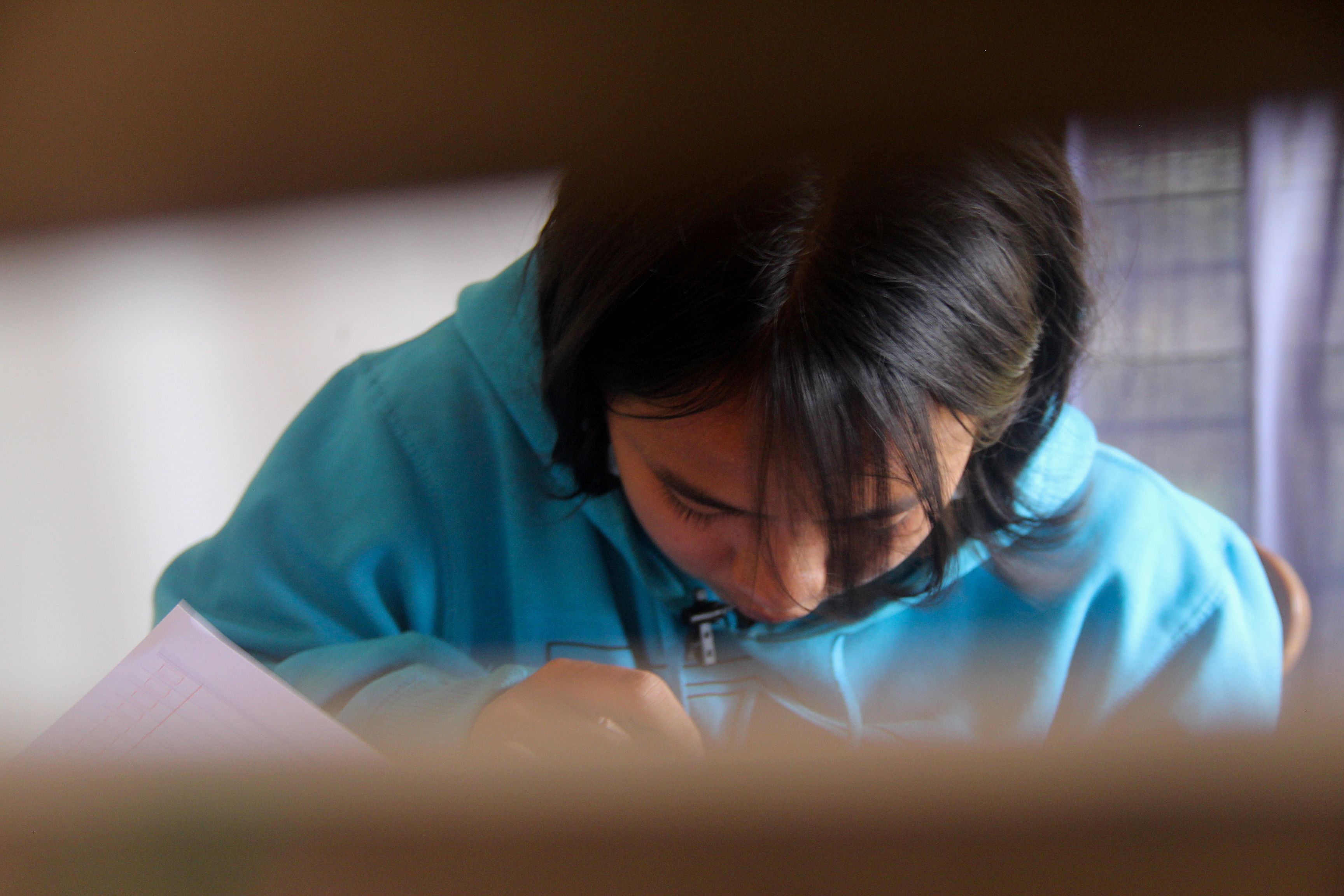 Ni Luh Nael, 13-years-old, writes in a book while studying at Bali Street Mums and Kids shelter, after dropping out of school during the coronavirus disease (COVID-19) pandemic, in Denpasar, Bali, Indonesia, September 10, 2021. Picture taken September 10, 2021. REUTERS/Wayan Sukarda