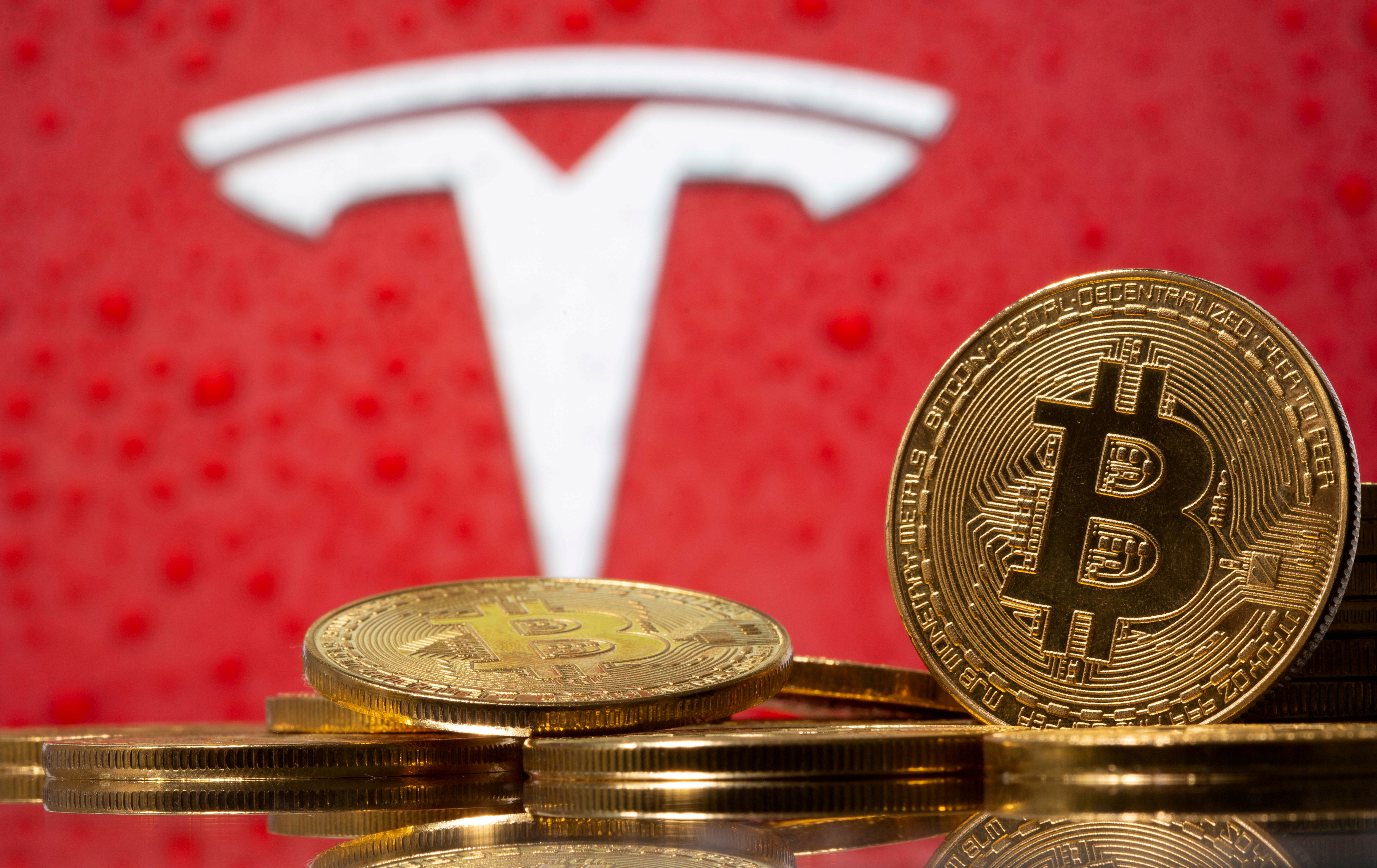 Representations of virtual currency bitcoin are seen in front of Tesla logo in this illustration taken, February 9, 2021. REUTERS/Dado Ruvic