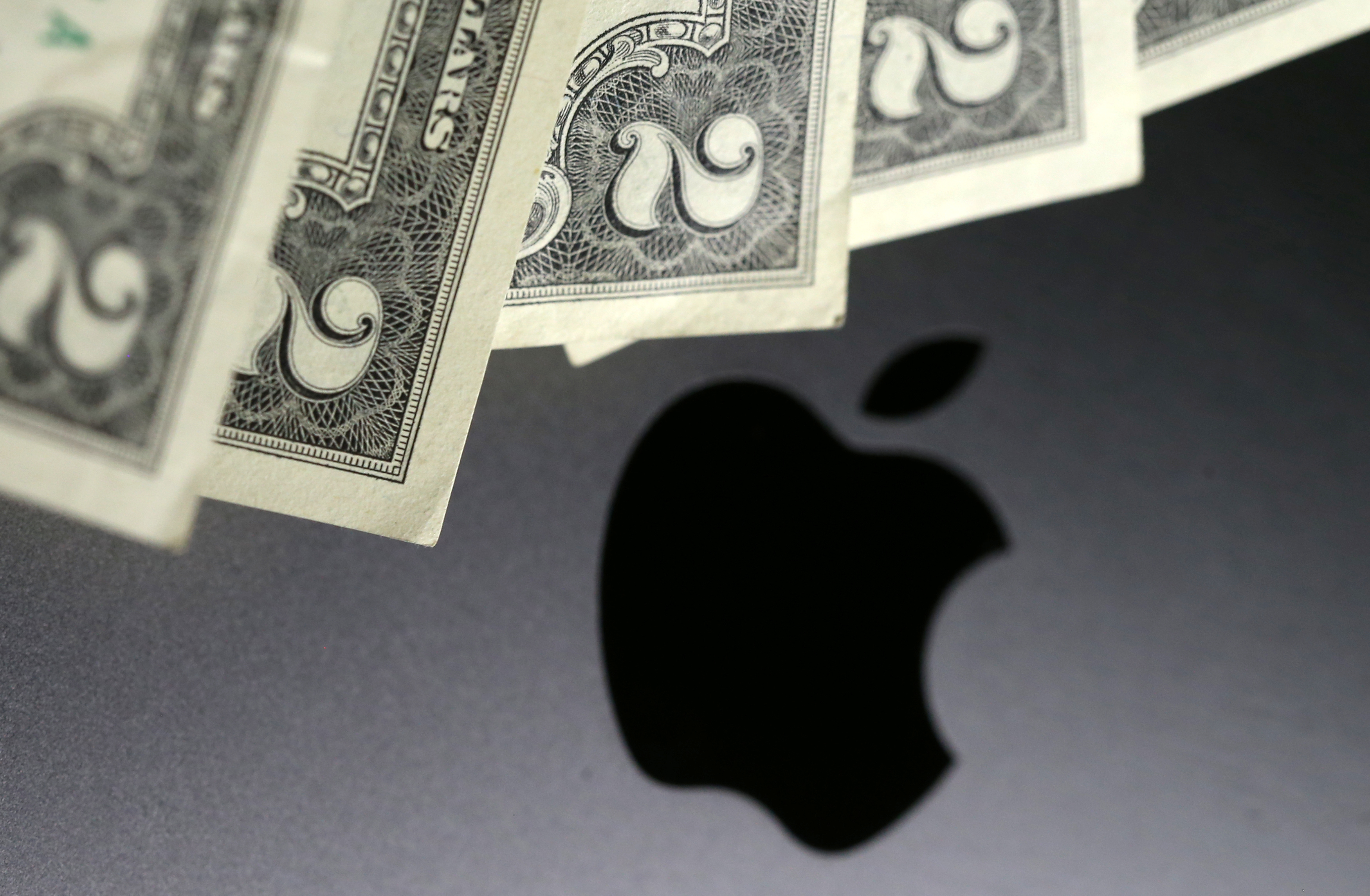 U.S. dollar banknotes are seen in front of the Apple logo in this photo illustration taken August 3, 2018. Photo illustration taken August 3, 2018. REUTERS/Dado Ruvic/Illustration