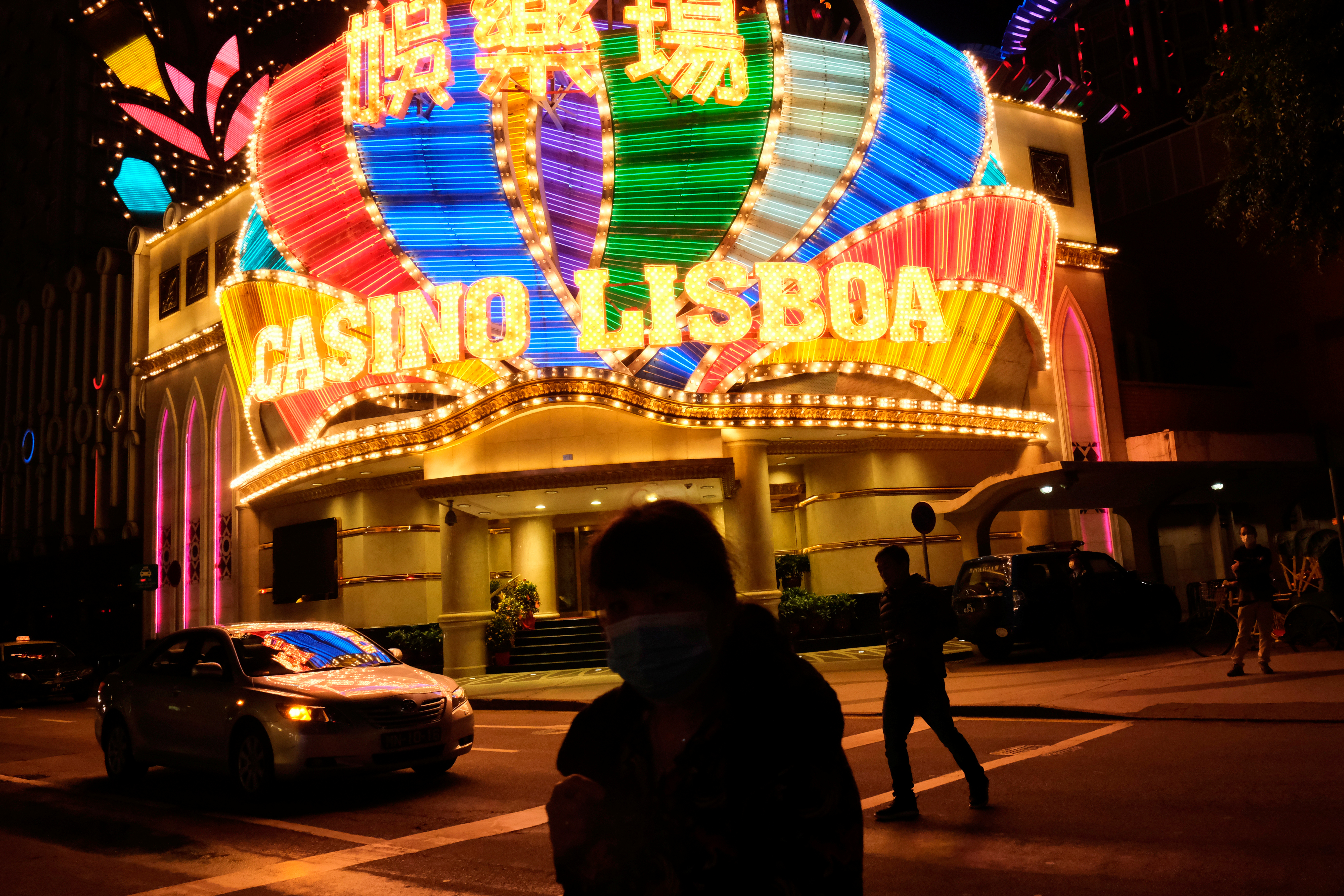 People wearing masks walk in front of Casino Lisboa, before its temporary closing, following the coronavirus outbreak in Macau, China February 4, 2020. REUTERS/Tyrone Siu