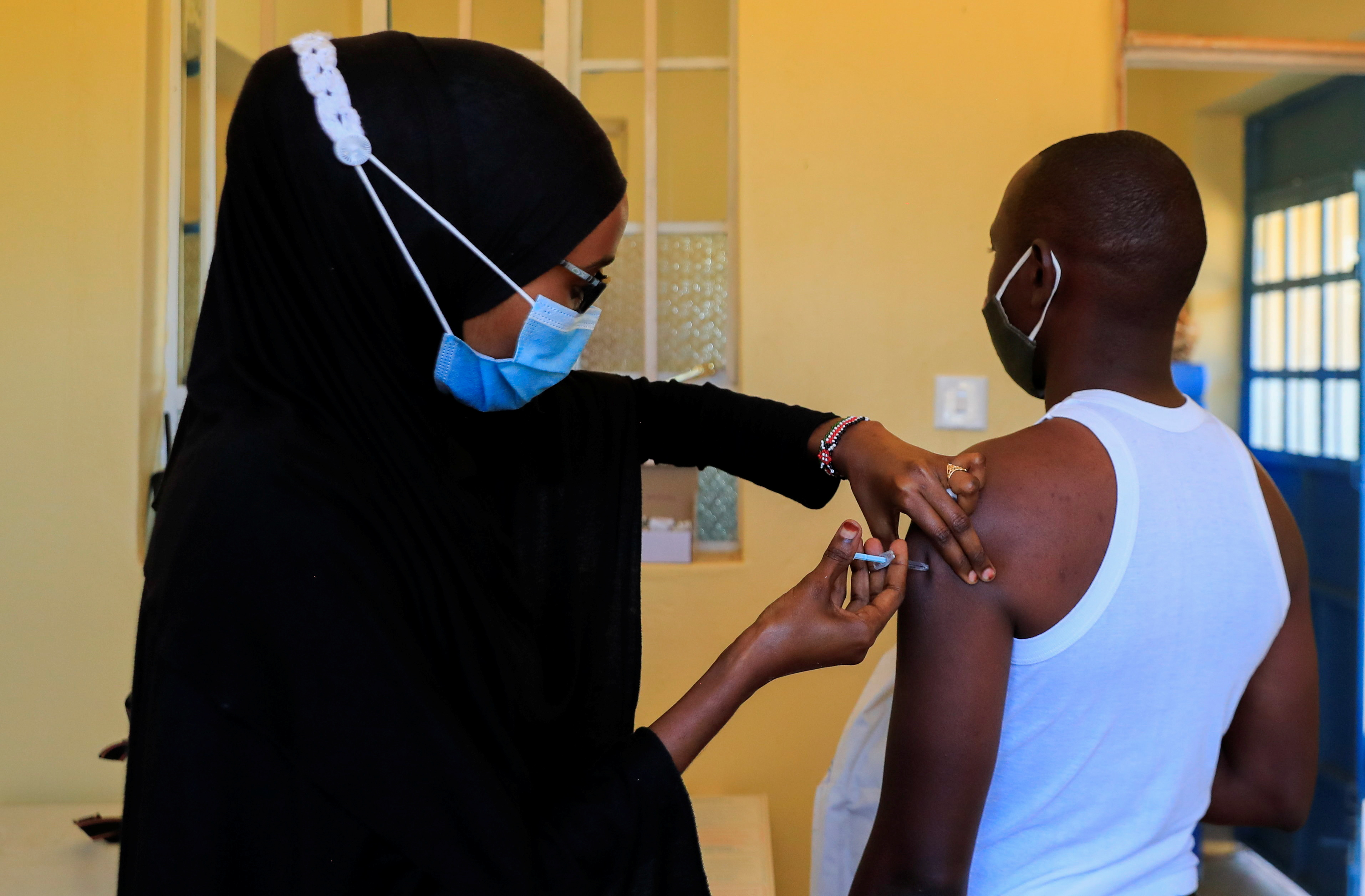 A nurse administers the coronavirus disease (COVID-19) vaccine to a man at the Bissil Health Centre within Iibissil settlement, Matapato North of Kajiado county, Kenya August 23, 2021. REUTERS/Thomas Mukoya