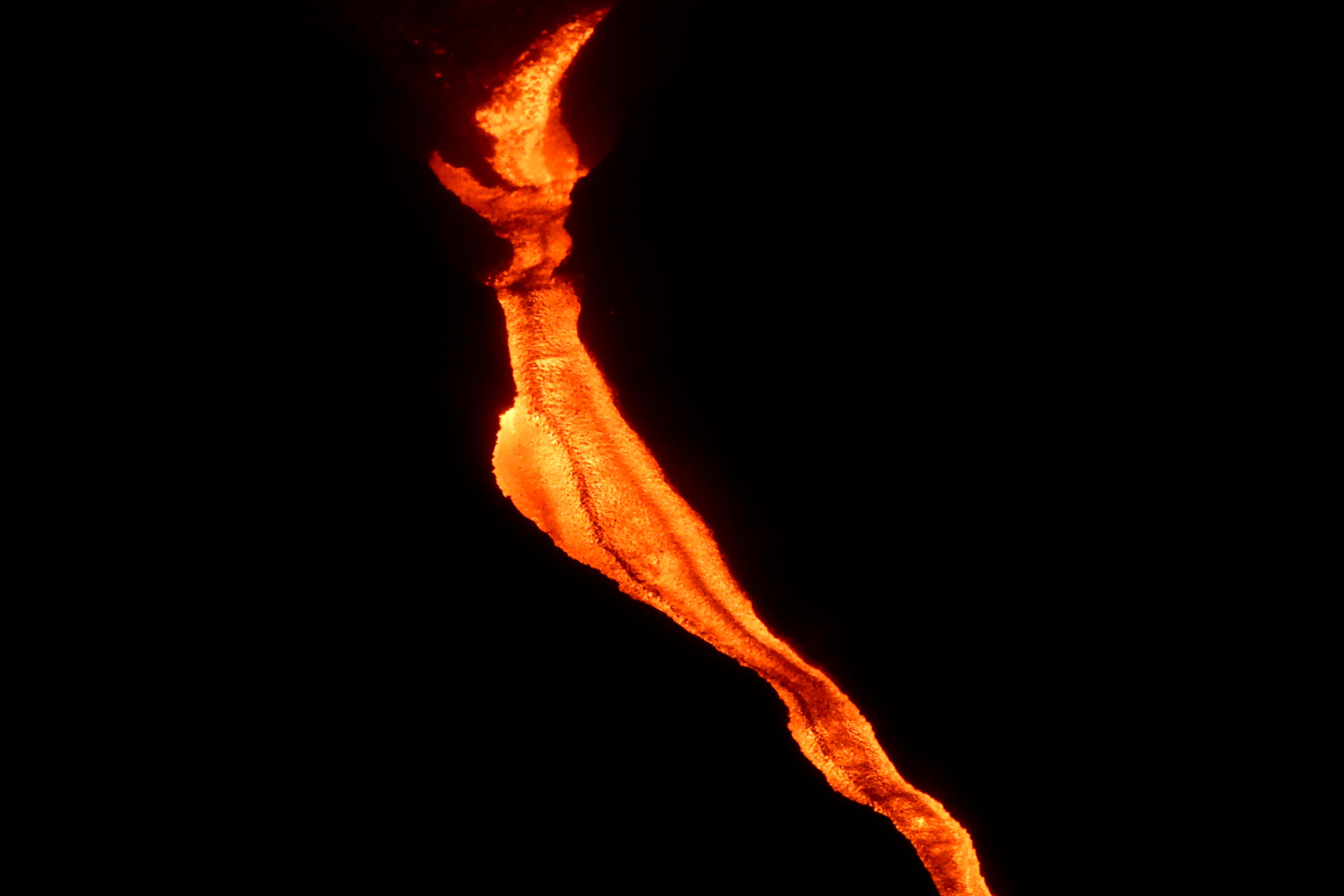 A lava, expelida do vulcão Cumbre Vieja, desce uma colina enquanto continua a entrar em erupção na ilha canária de La Palma, vista de Tacande, Espanha, 12 de outubro de 2021. REUTERS / Sergio Perez
