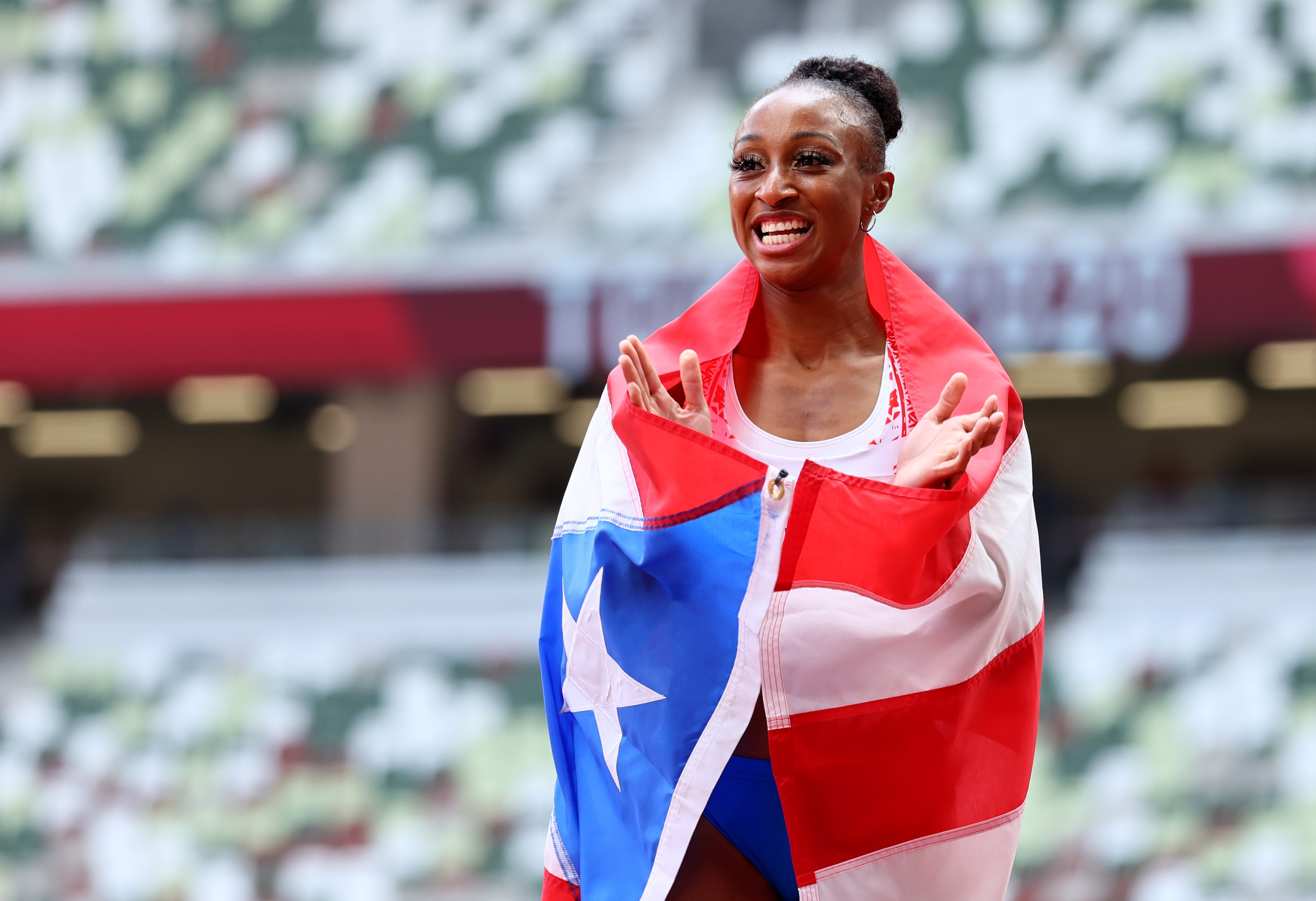 Tokyo 2020 Olympics - Athletics - Women's 100m Hurdles - Final - Olympic Stadium, Tokyo, Japan - August 2, 2021. Jasmine Camacho-Quinn of Puerto Rico celebrates with her national flag after winning gold REUTERS/Lucy Nicholson