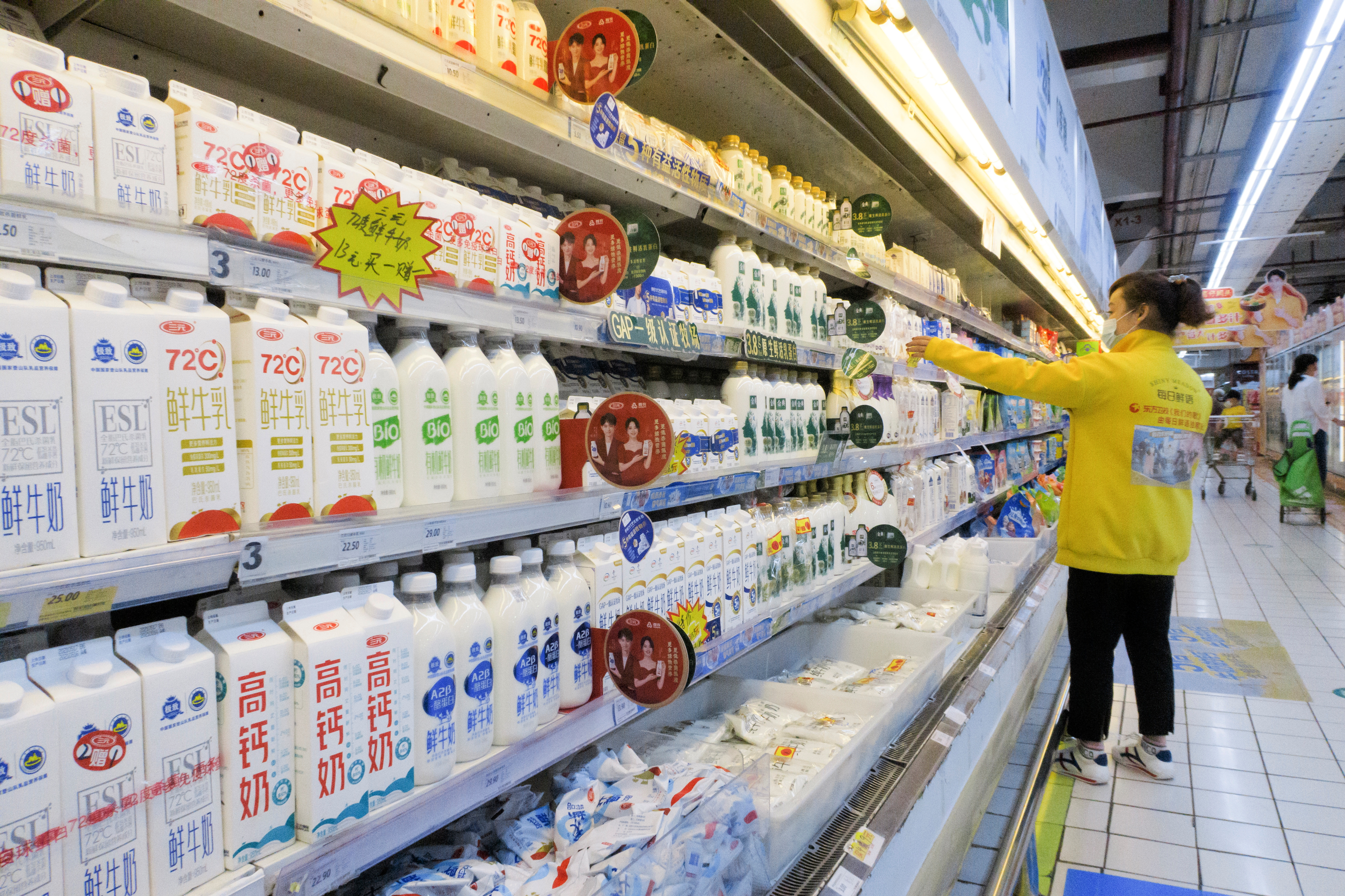 A staff member arranges cartons of milk on refrigerator shelves at a supermarket in Beijing, China, May 21, 2021. REUTERS/Thomas Peter