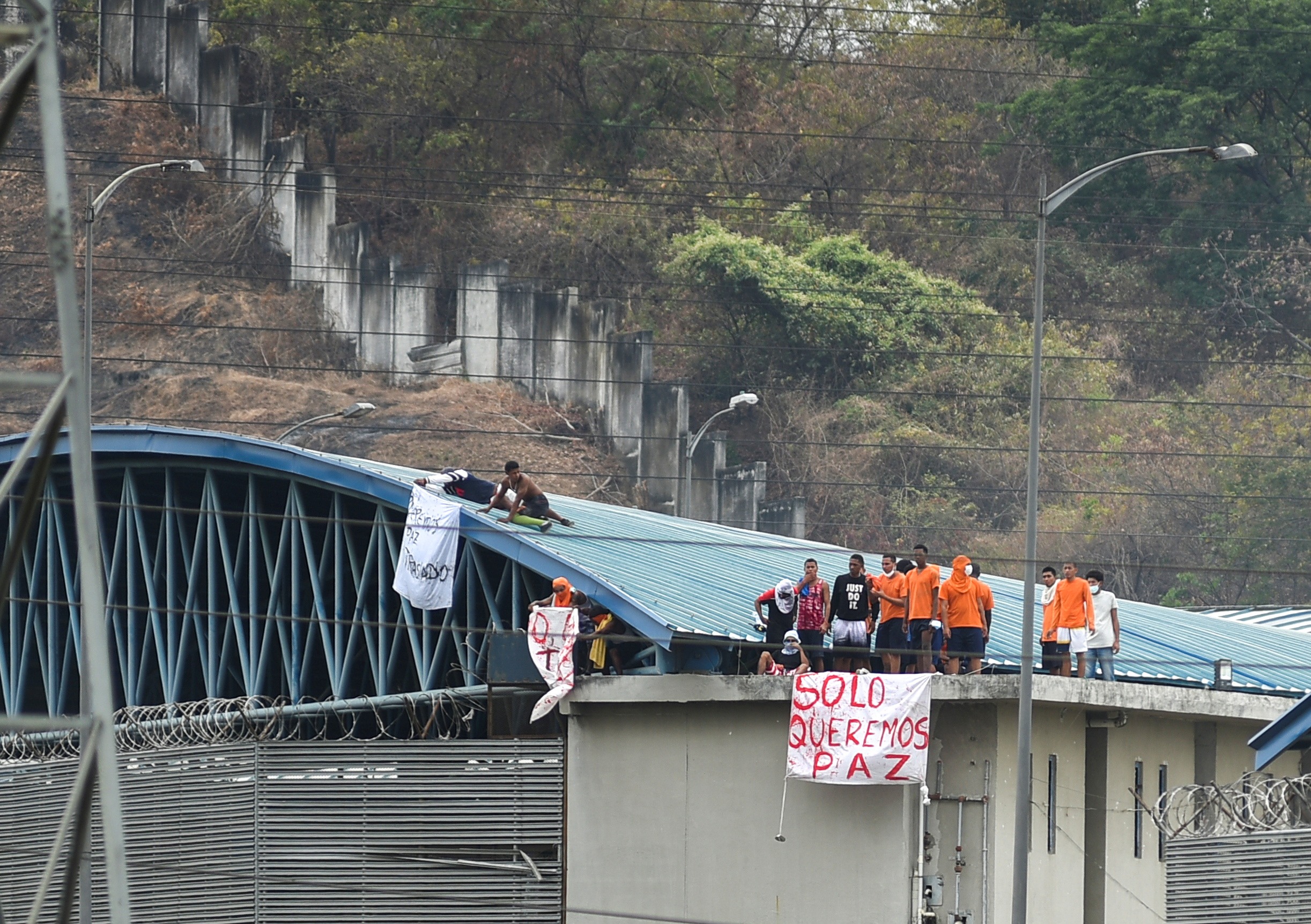 Inmates of the Regional de Guayaquil prison hold banners reading